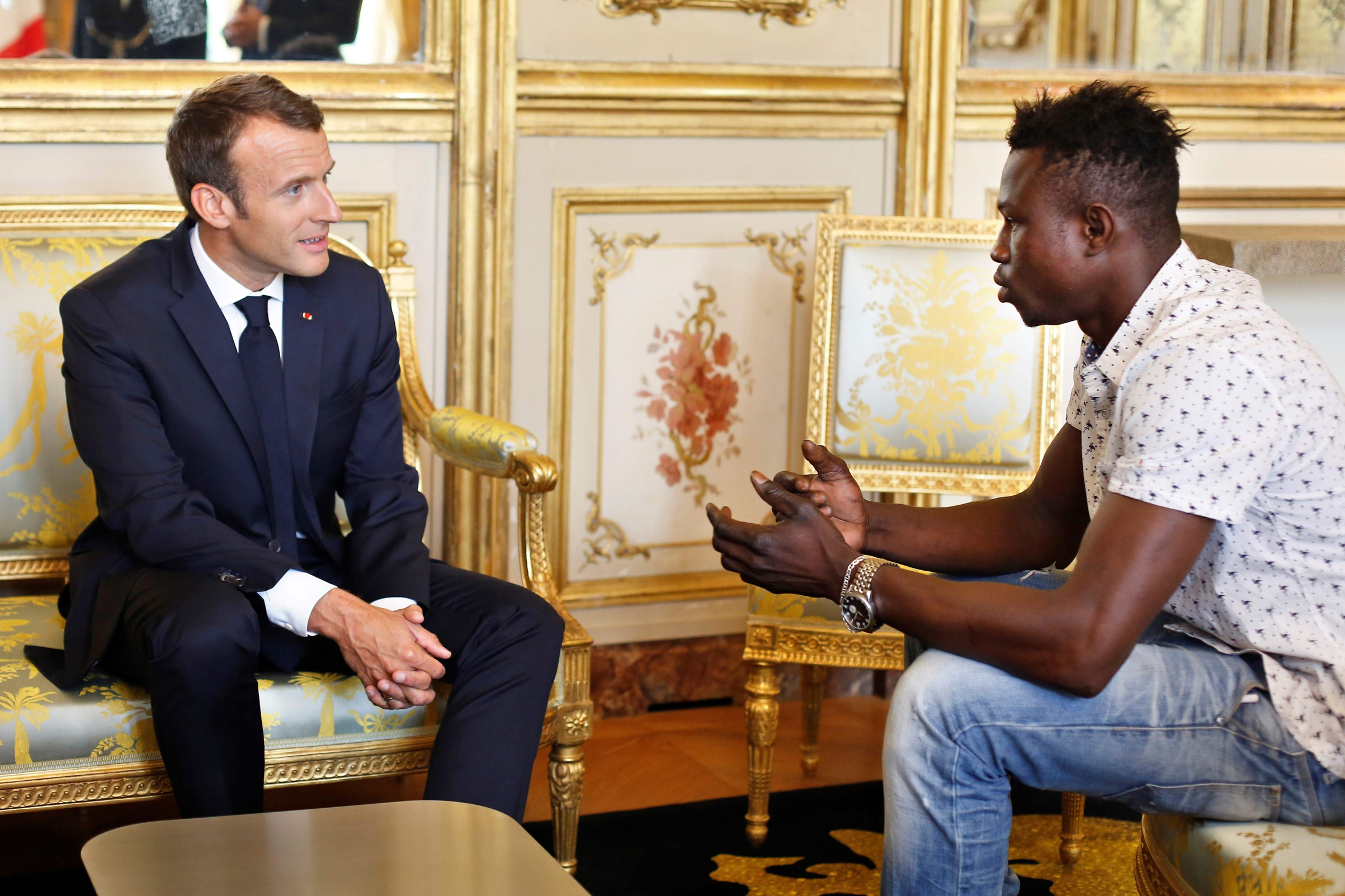 French President Emmanuel Macron speaks with Mamoudou Gassama, 22, from Mali, at the presidential Élysée Palace in Paris on May, 28, 2018. Gassama, living illegally in France, is being honored by Macron for scaling an apartment building to save a child who was dangling from a fifth-floor balcony.