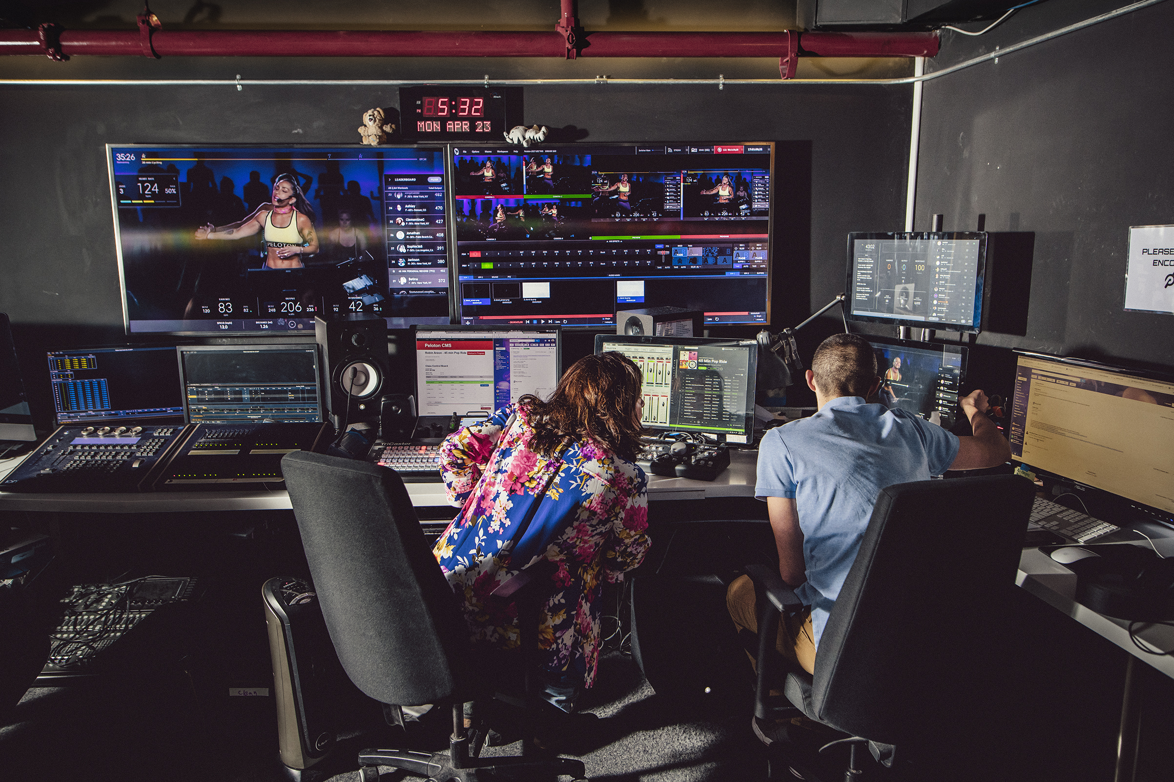 Peloton's production technicians Samantha Pirrello, left, and Joe Palagonia edit a live stream of Arzon's cycling class in New York City for riders at home