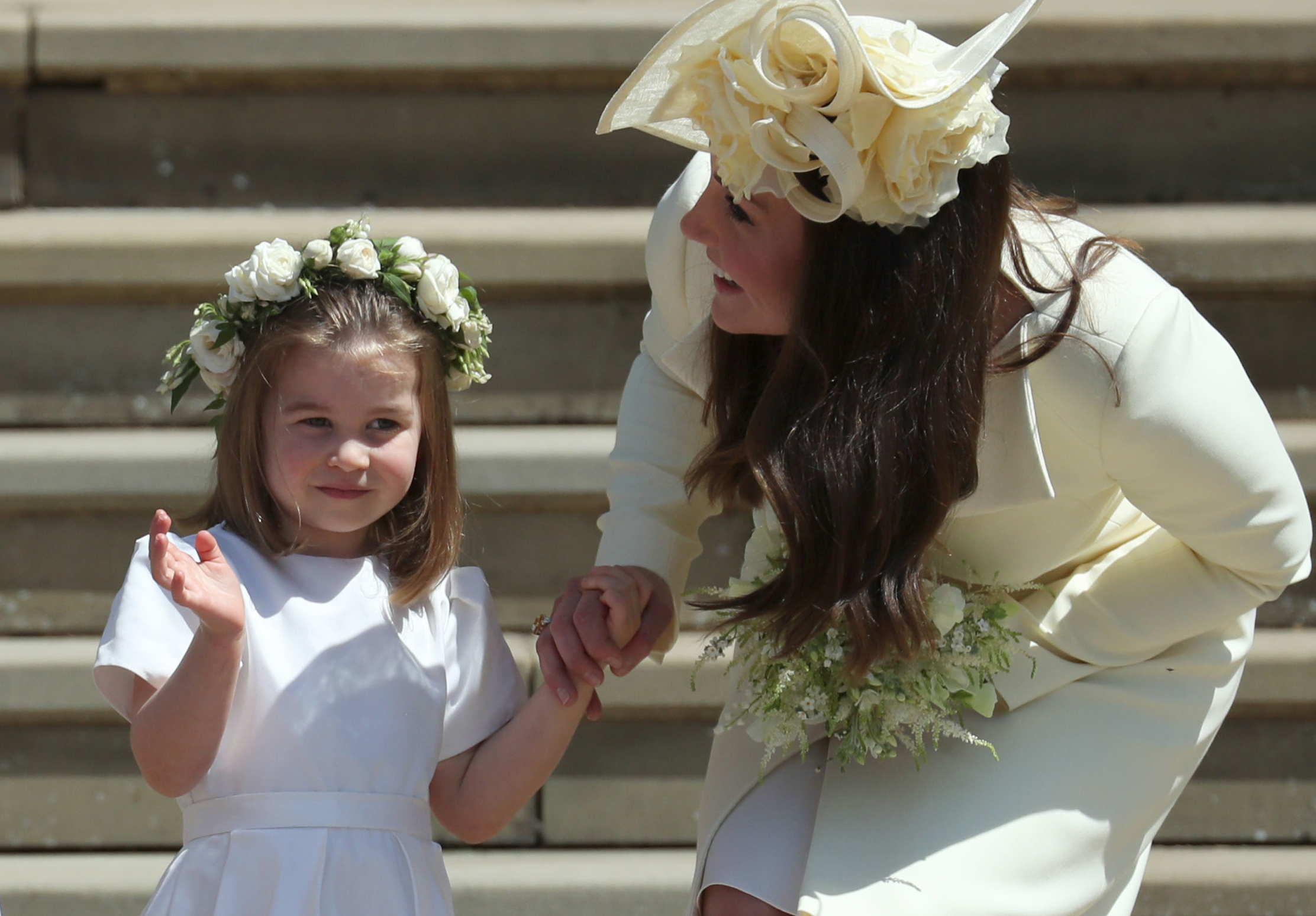 Princess Charlotte (L) waves by her mother Britain's Catherine, Duchess of Cambridge after attending the wedding ceremony of Britain's Prince Harry, Duke of Sussex and US actress Meghan Markle at St George's Chapel, Windsor Castle, in Windsor, on May 19, 2018.