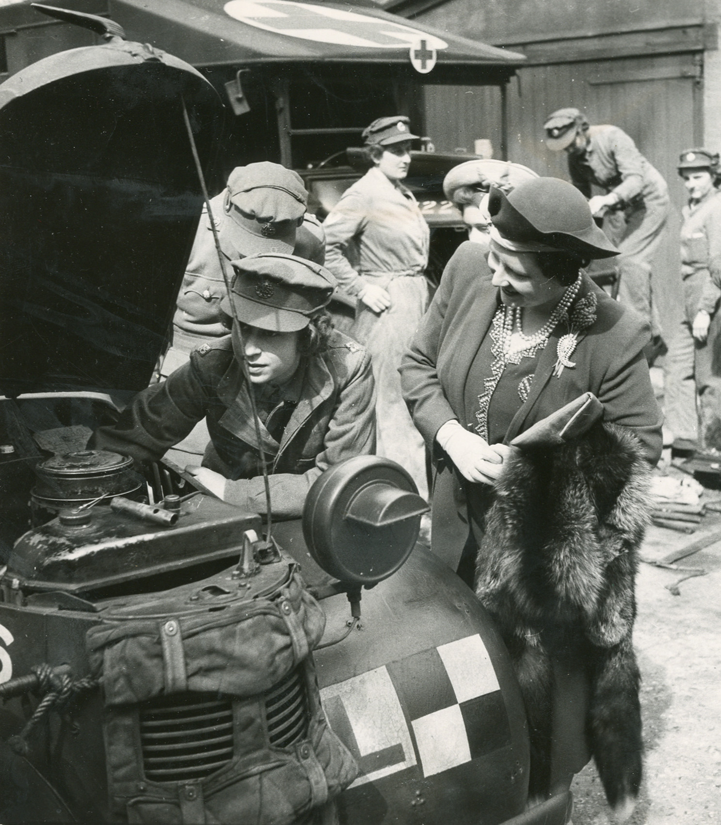 Princess Elizabeth explains to the Queen what she has done to the car engine. April, 1945.