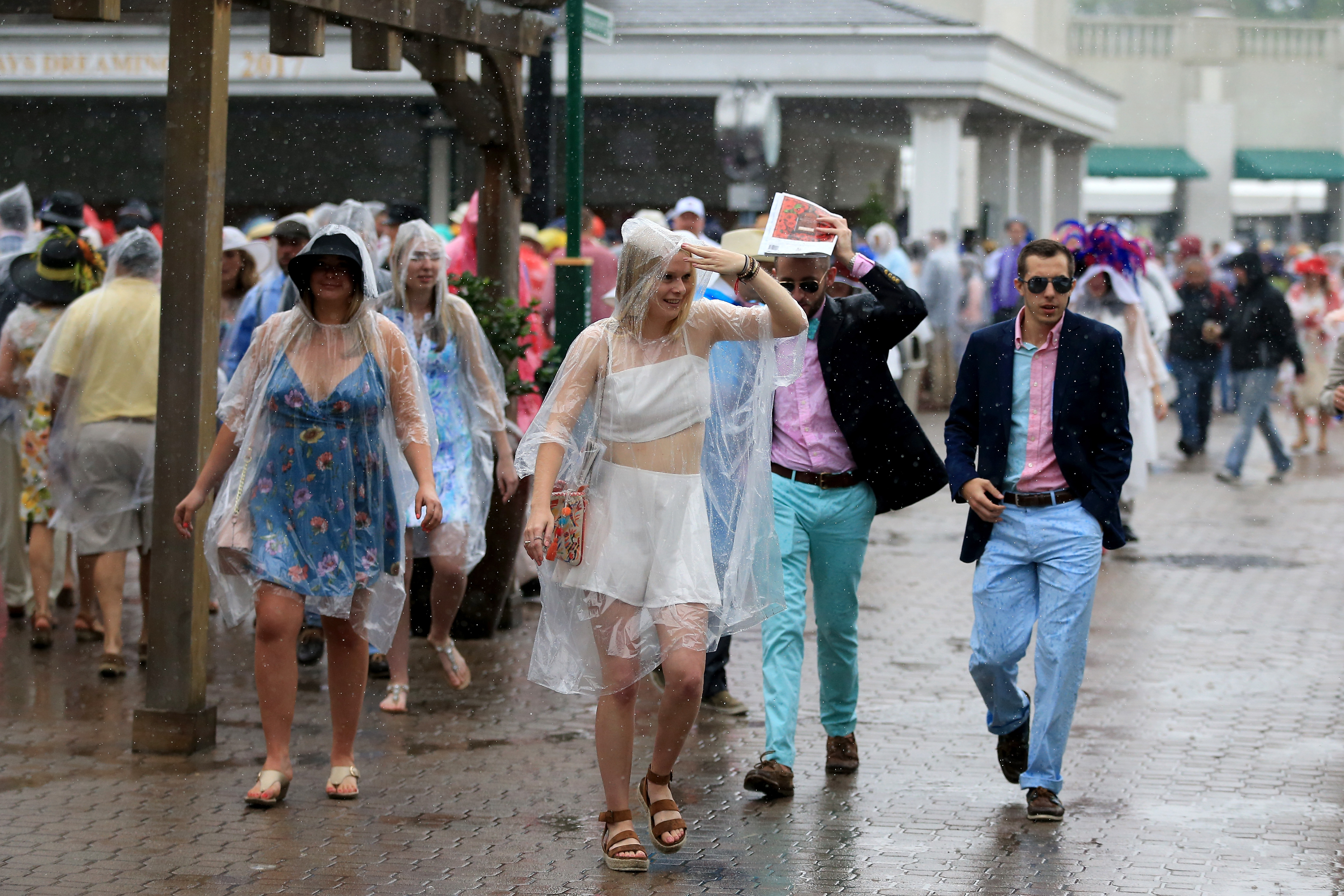 Patrons deal with rain prior to the 144th running of the Kentucky Derby at Churchill Downs on May 5, 2018 in Louisville