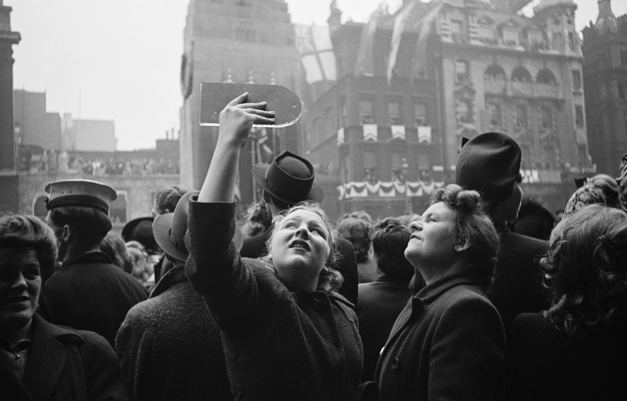 Spectators use hand-held mirrors to see over the crowd during the wedding of Queen Elizabeth II and Prince Philip, Duke of Edinburgh, at Westminster Abbey in London, Nov. 20, 1947.