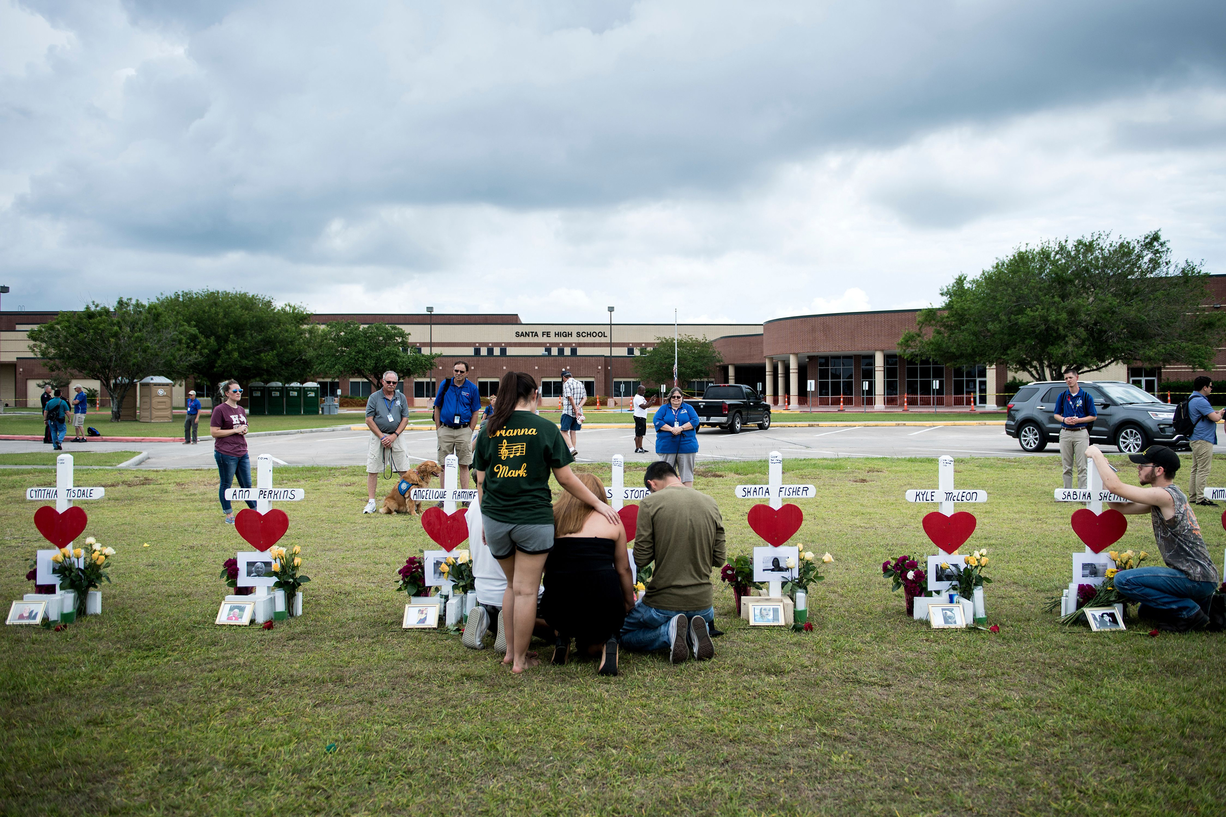 People visit a cross for Christopher Stone at a memorial for the victims of the Santa Fe High School shooting on May 21, 2018 in Santa Fe, Texas.