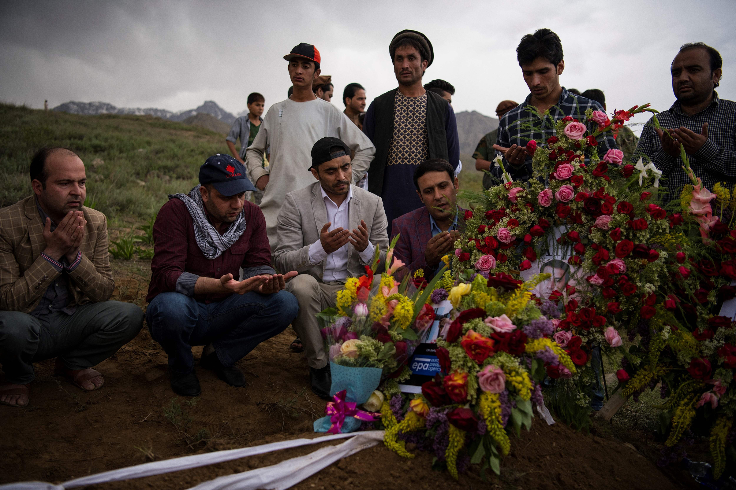 Friends and relatives of Marai at his grave in the village of Guldara