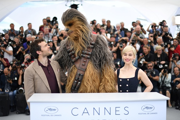 U.S. actor Alden Ehrenreich, Chewbacca and British actor Emilia Clarke pose on May 15, 2018 during a photocall for the film 'Solo : A Star Wars Story' at the 71st edition of the Cannes Film Festival in Cannes, southern France.
