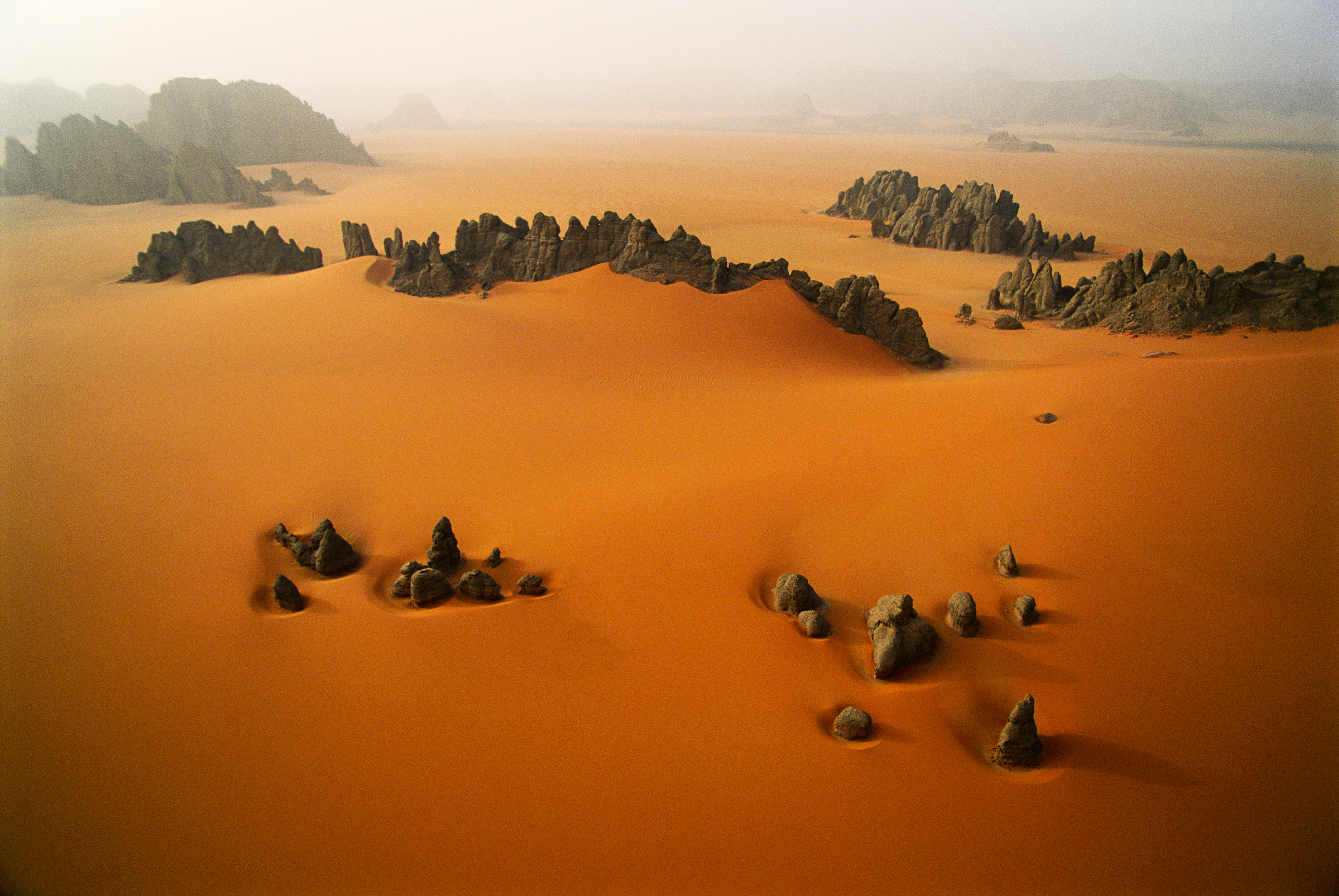 Pinnacles of sandstone rise through the orange dunes of the Karnasai Valley, Chad. Photographed from a paraglider.