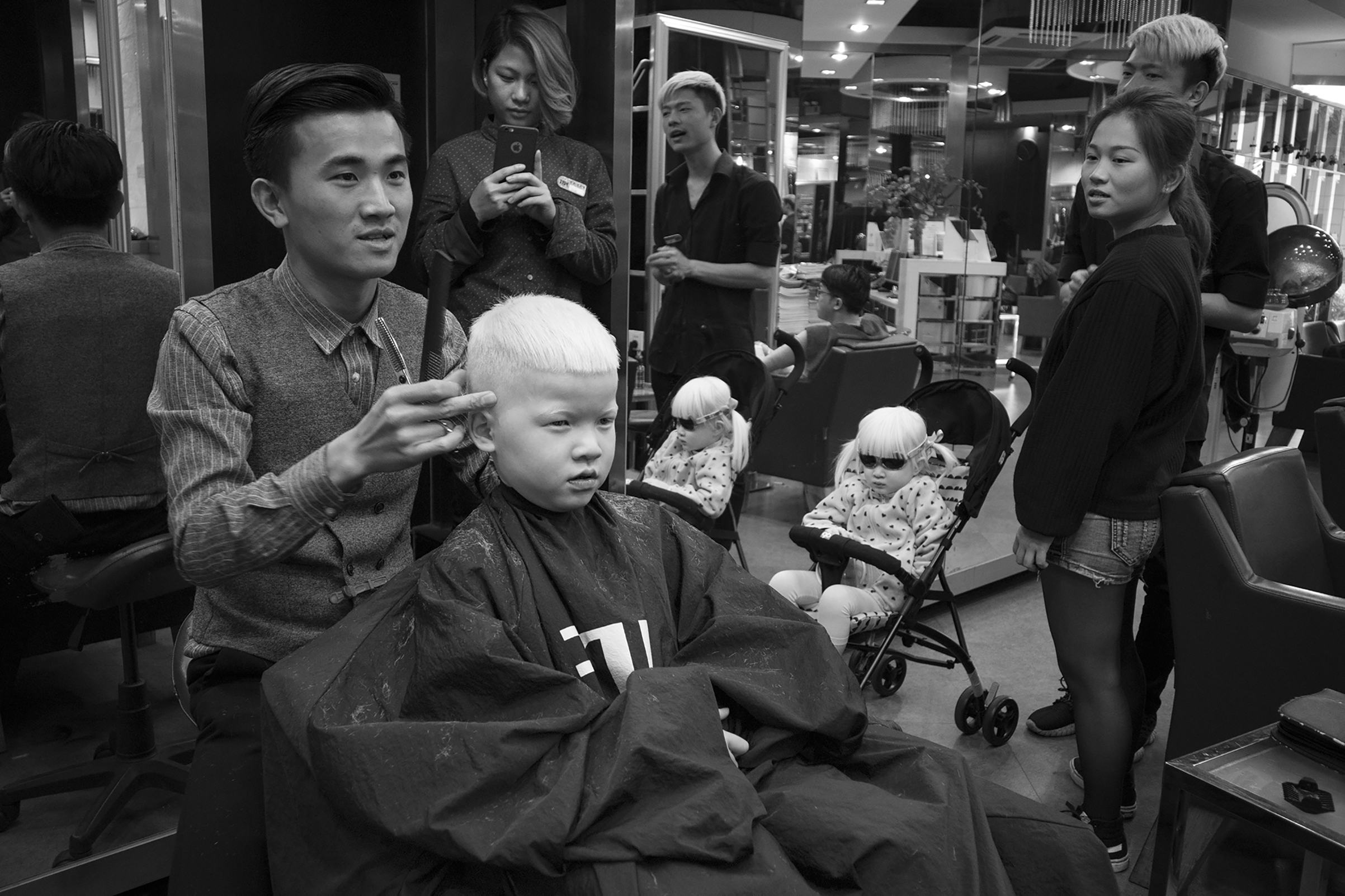 Forest gets a haircut in Guangzhou, China as Lotus watches from a stroller. Adopting both children at once required a three week trip to China.