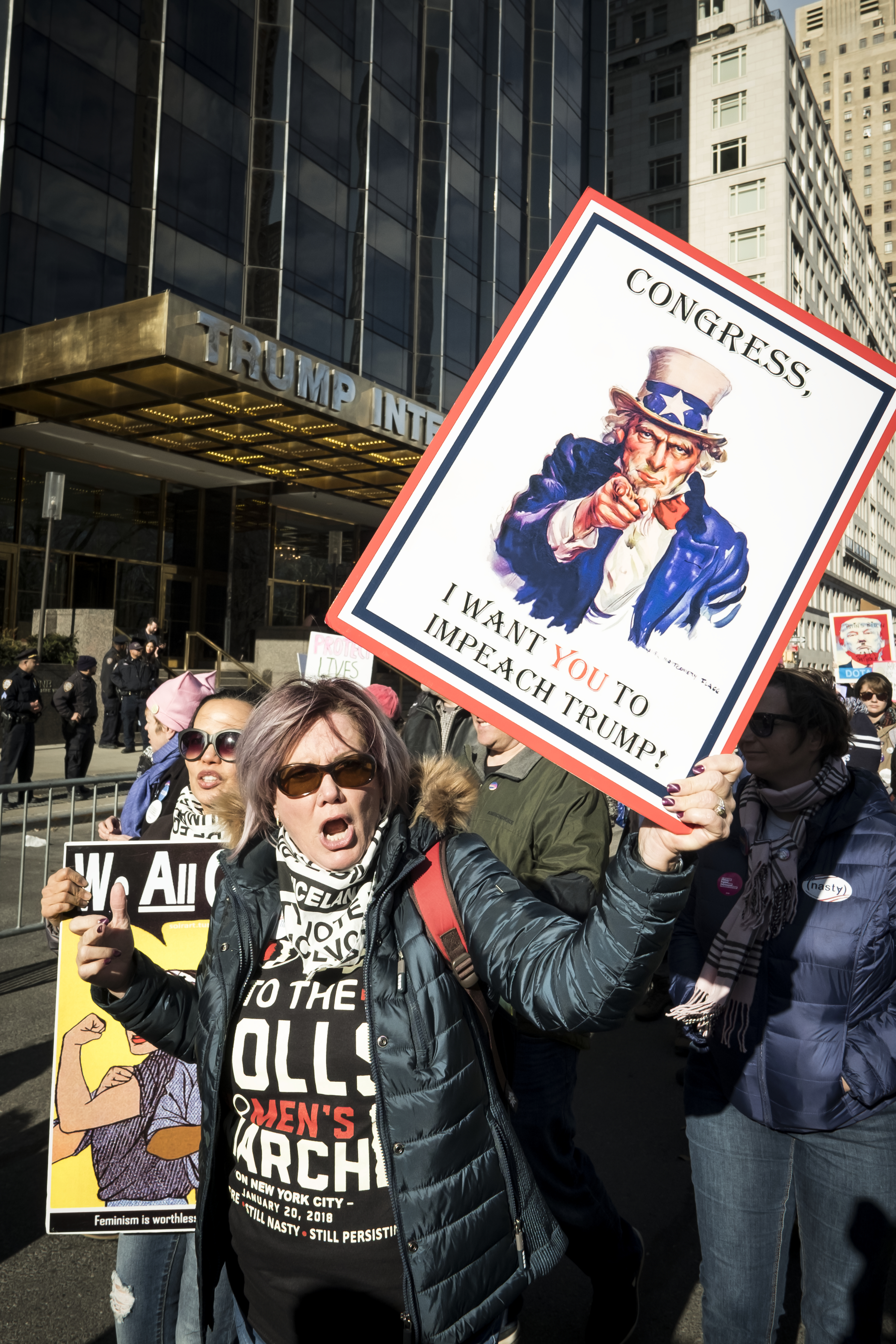 NEW YORK, NY - JANUARY 20: A demonstrator holds up a  banner saying  Congress, I Want You To Impeach Trump  in front of Trump International Hotel and Tower during the second annual Women's March in the borough of Manhattan in New York City, U.S. on Saturday, January 20, 2018.