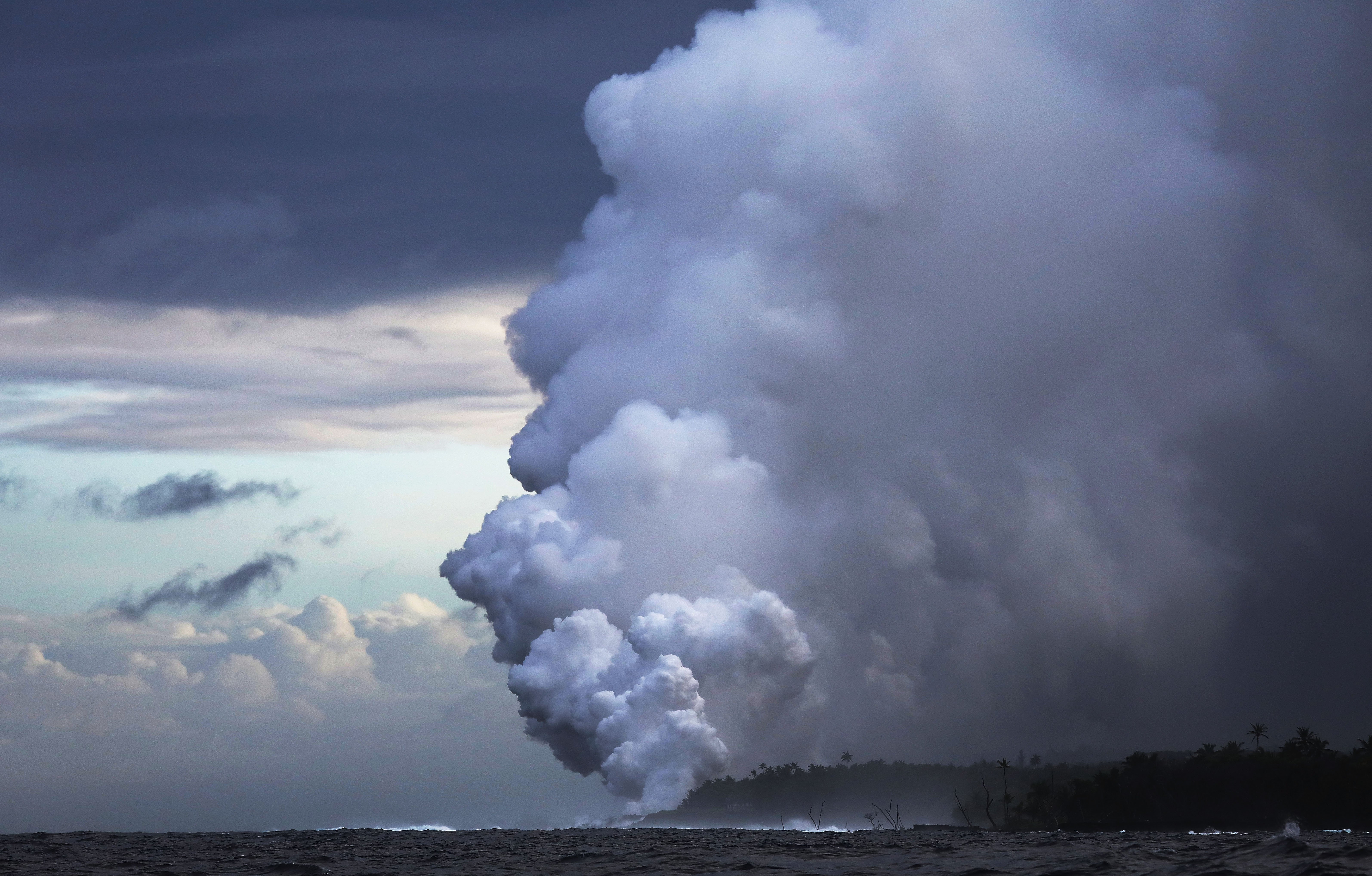 A steam plume rises from lava entering the Pacific Ocean, after flowing to the water from a Kilauea volcano fissure, on Hawaii's Big Island on May 20, 2018 near Pahoa, Hawaii.