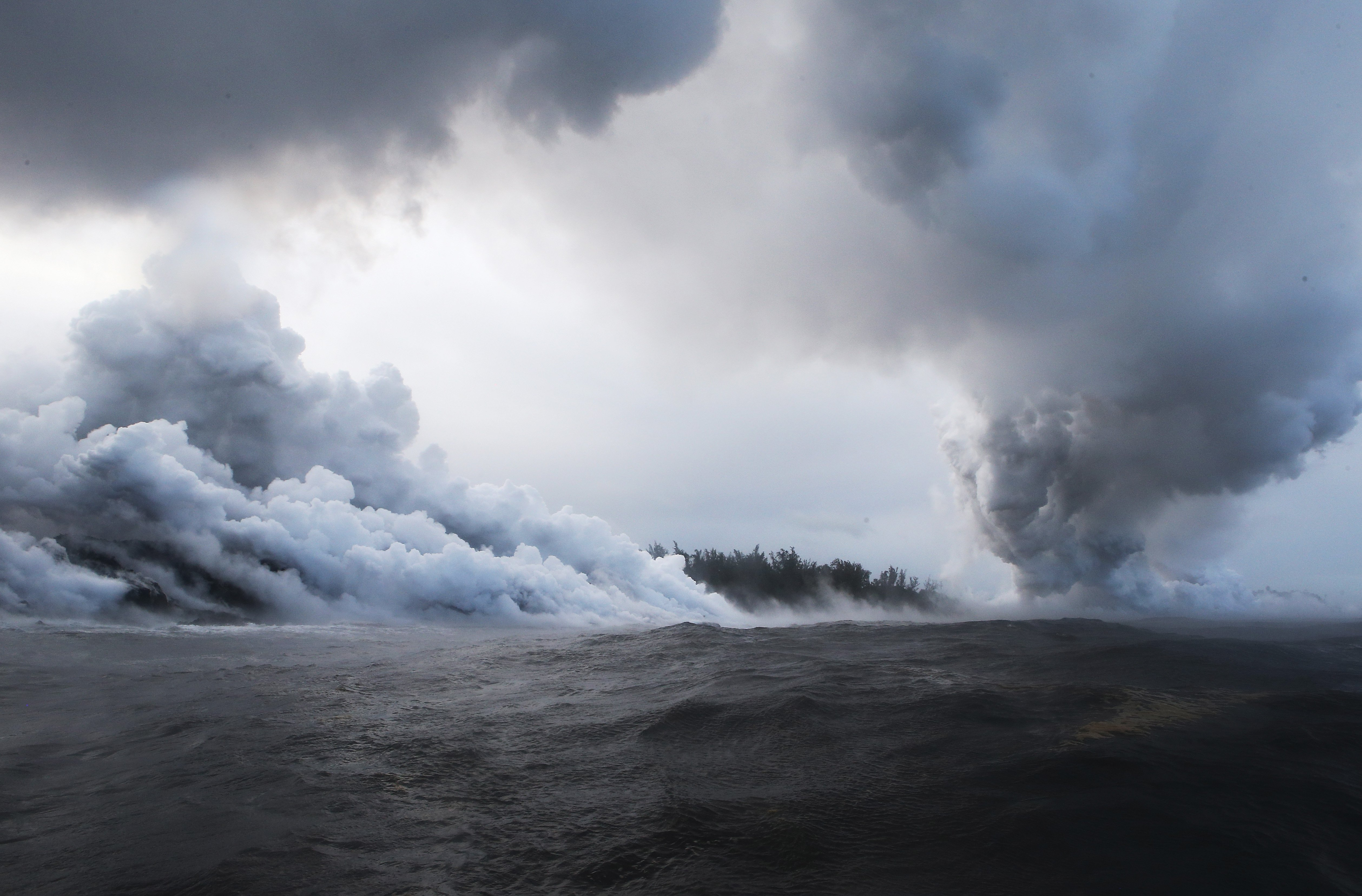 A steam plume rises from lava entering the Pacific Ocean, after flowing to the water from a Kilauea volcano fissure, on Hawaii's Big Island on May 20, 2018 in Pahoa, Hawaii.