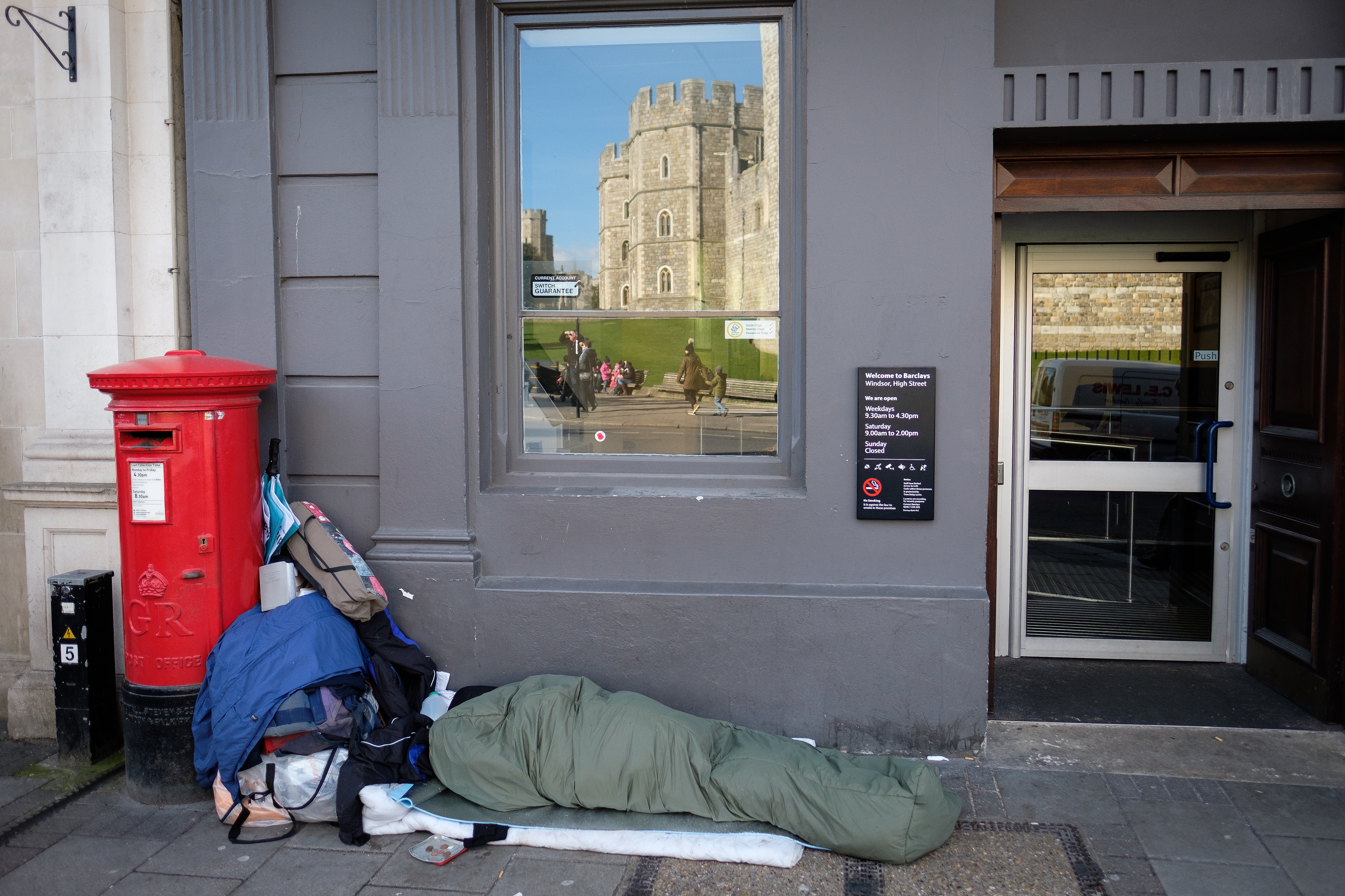 Windsor Castle is seen in the reflection of a bank window as Sunny, a homeless man who has been on the streets of Windsor for around eight months, lays in his sleeping bag on January 5, 2018 in Windsor, England.
