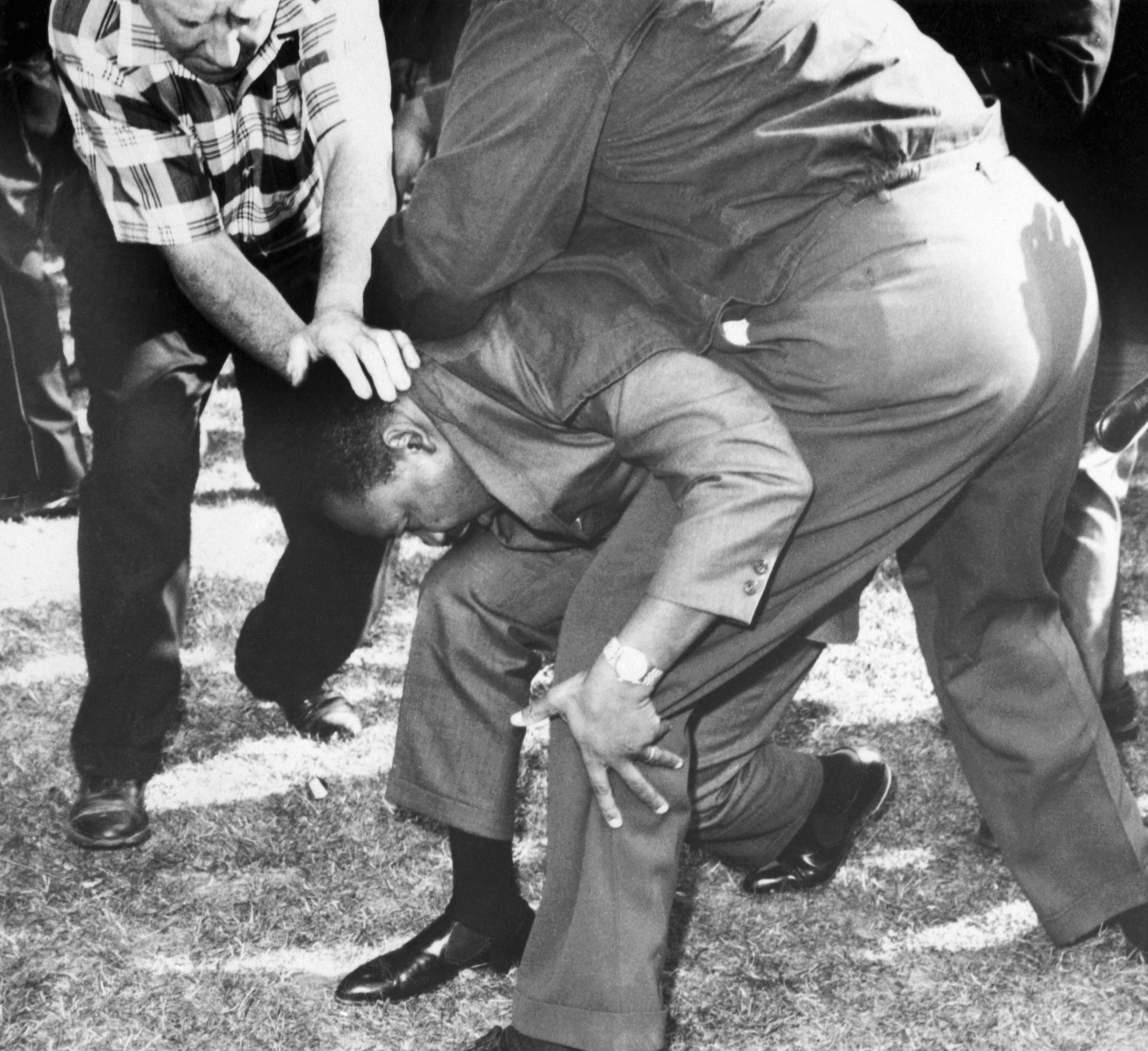 Struck on the head by a rock thrown by a group of hecklers in Chicago, Dr. Martin Luther King falls to one knee. Aug. 5, 1966.