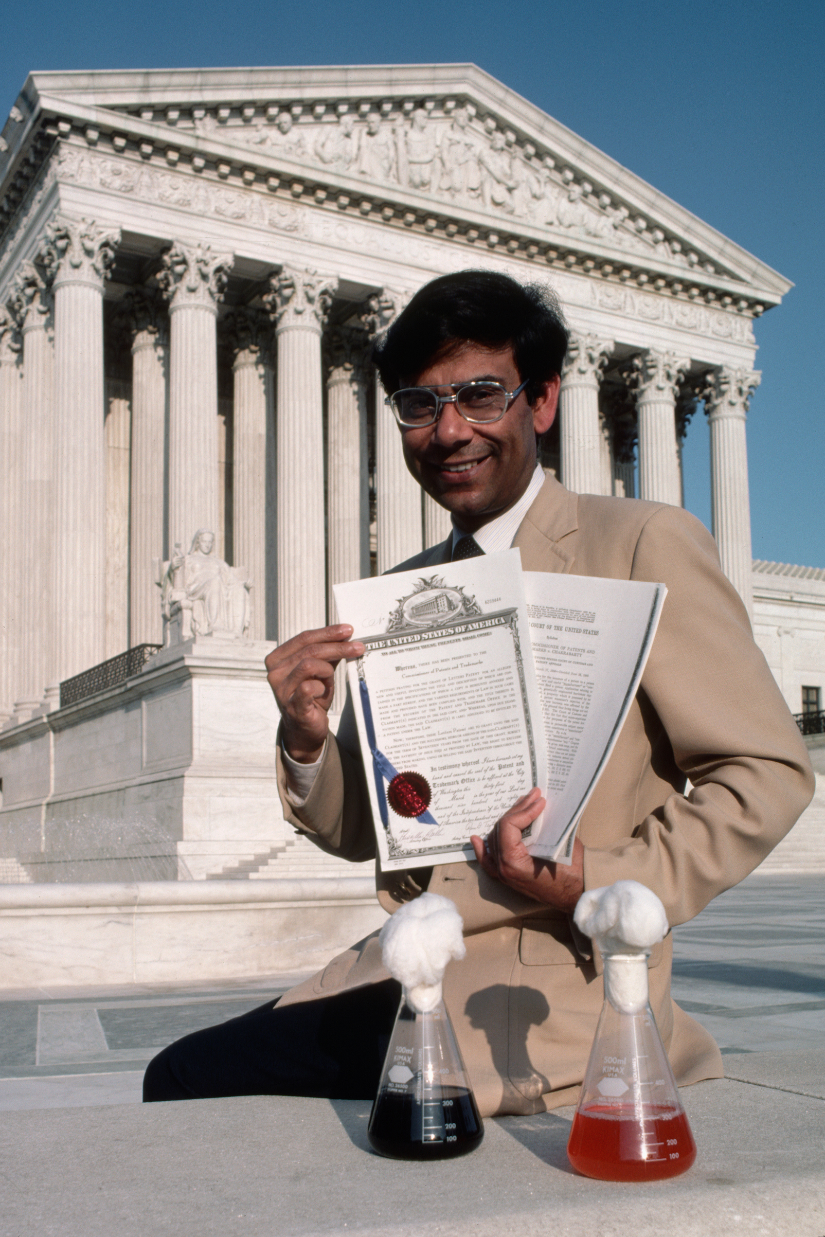 In front of the Supreme Court of the United States, Dr. Ananda Chakrabarty displays a trio of souvenirs of his pioneering experiments with a recombinant DNA created oil spill-eating bacteria.