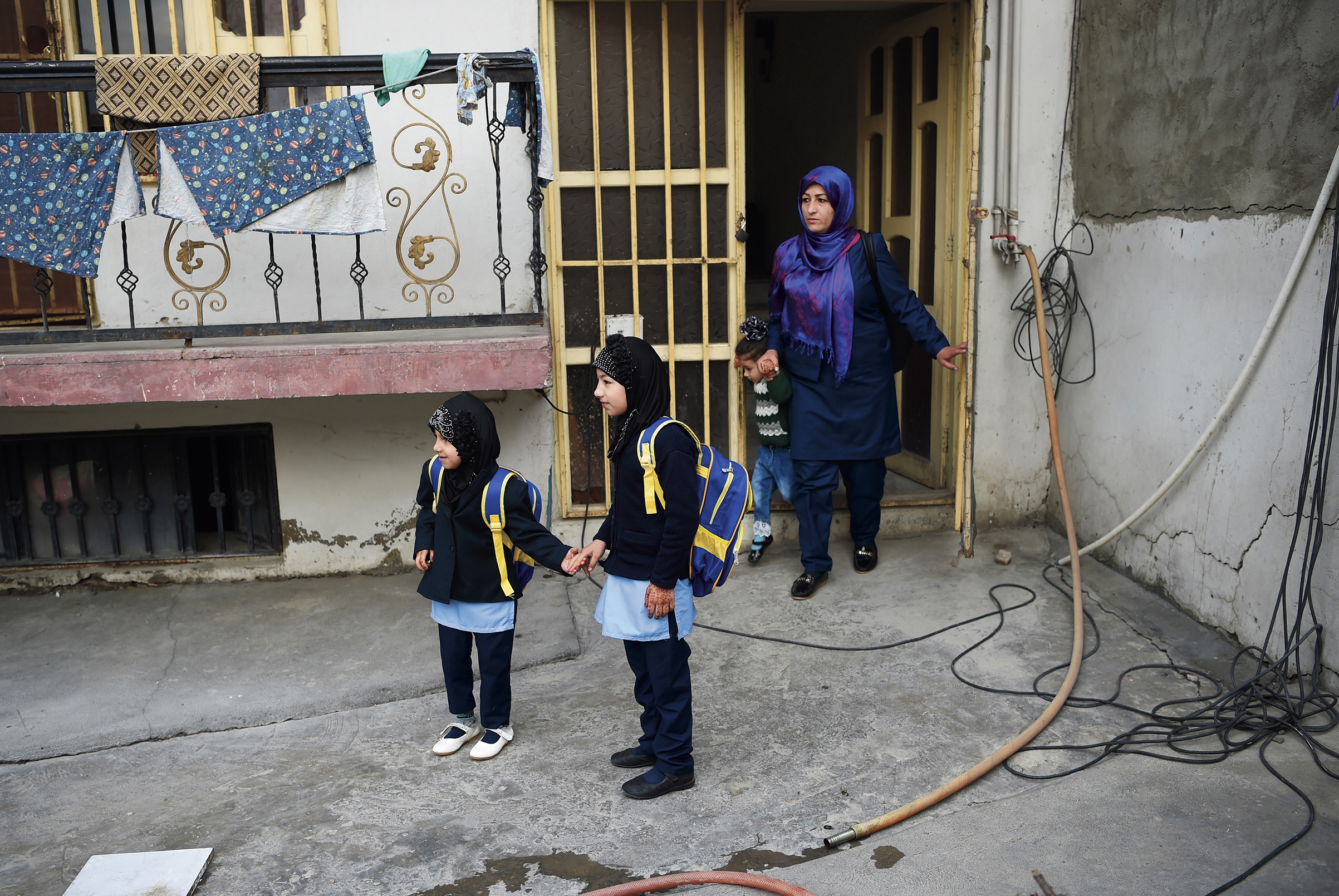 A mother and her three daughters set out for the first day of the school year in Kabul, on March 24