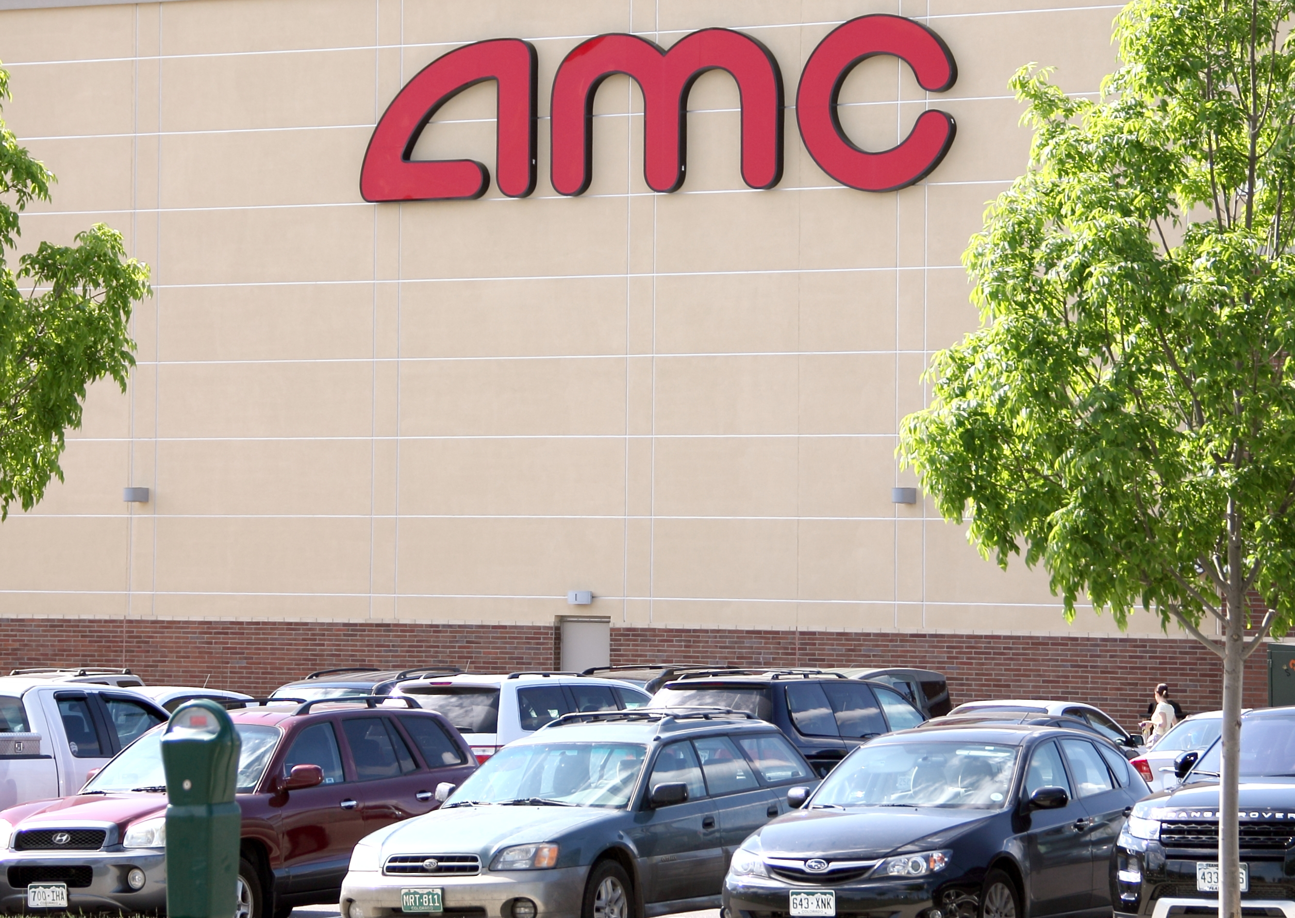 Westminster,  U.S.A. - May 6, 2012:  A parking lot full of movie goer's vehicles, and movie goer's approaching the entrance.  A large 'AMC' sign in red on cream colored stone,  movie goers approaching the entrance.