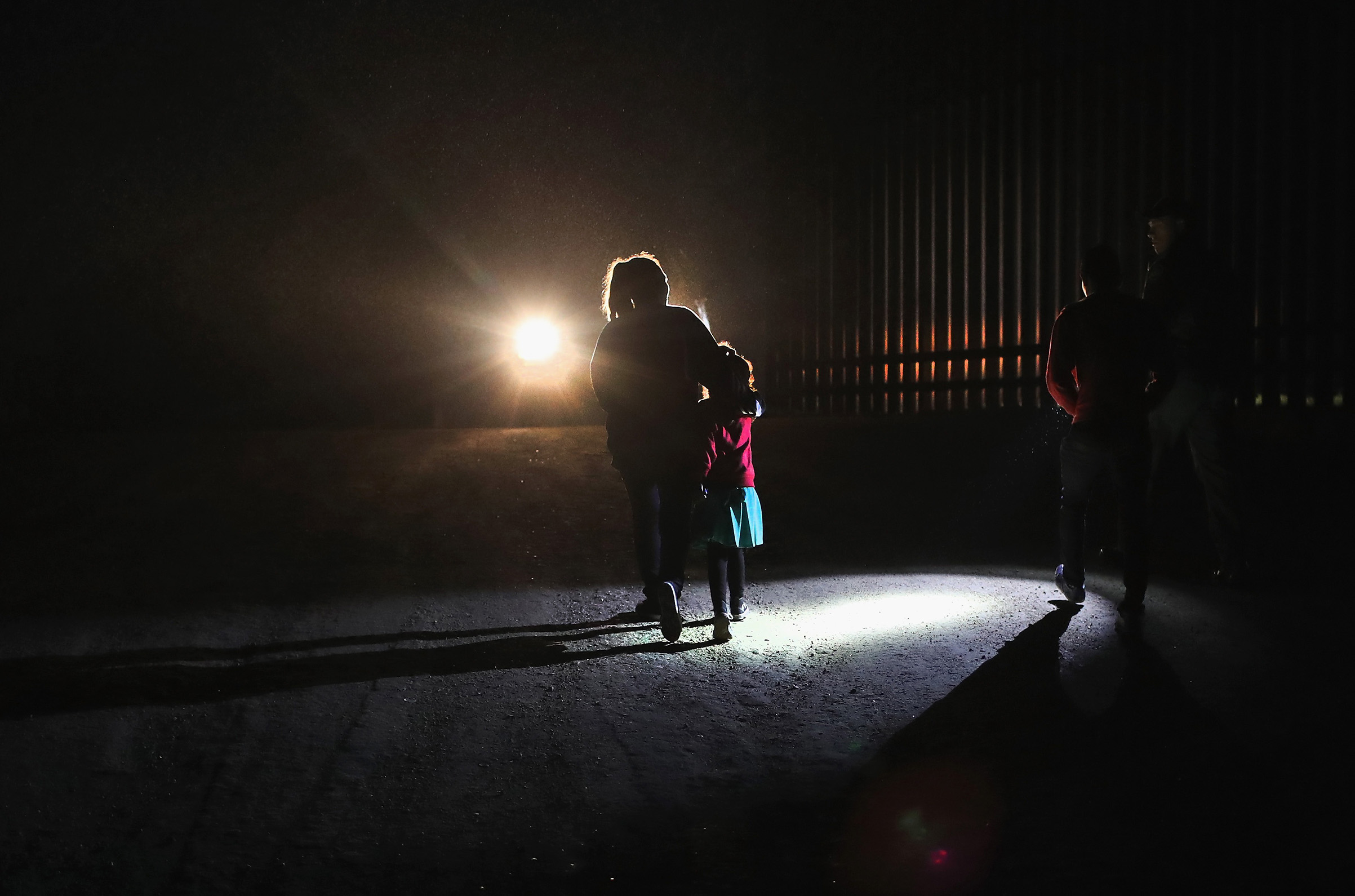 A Honduran mother walks with her children next to the U.S.-Mexico border fence as they turned themselves in to Border Patrol agents on February 22, 2018 near Penitas, Texas. Thousands of Central American families continue to enter the U.S., most seeking political asylum from violence in their home countries. The Rio Grande Valley has the highest number of undocumented immigrant crossings and narcotics smuggling of the entire U.S.-Mexico border.