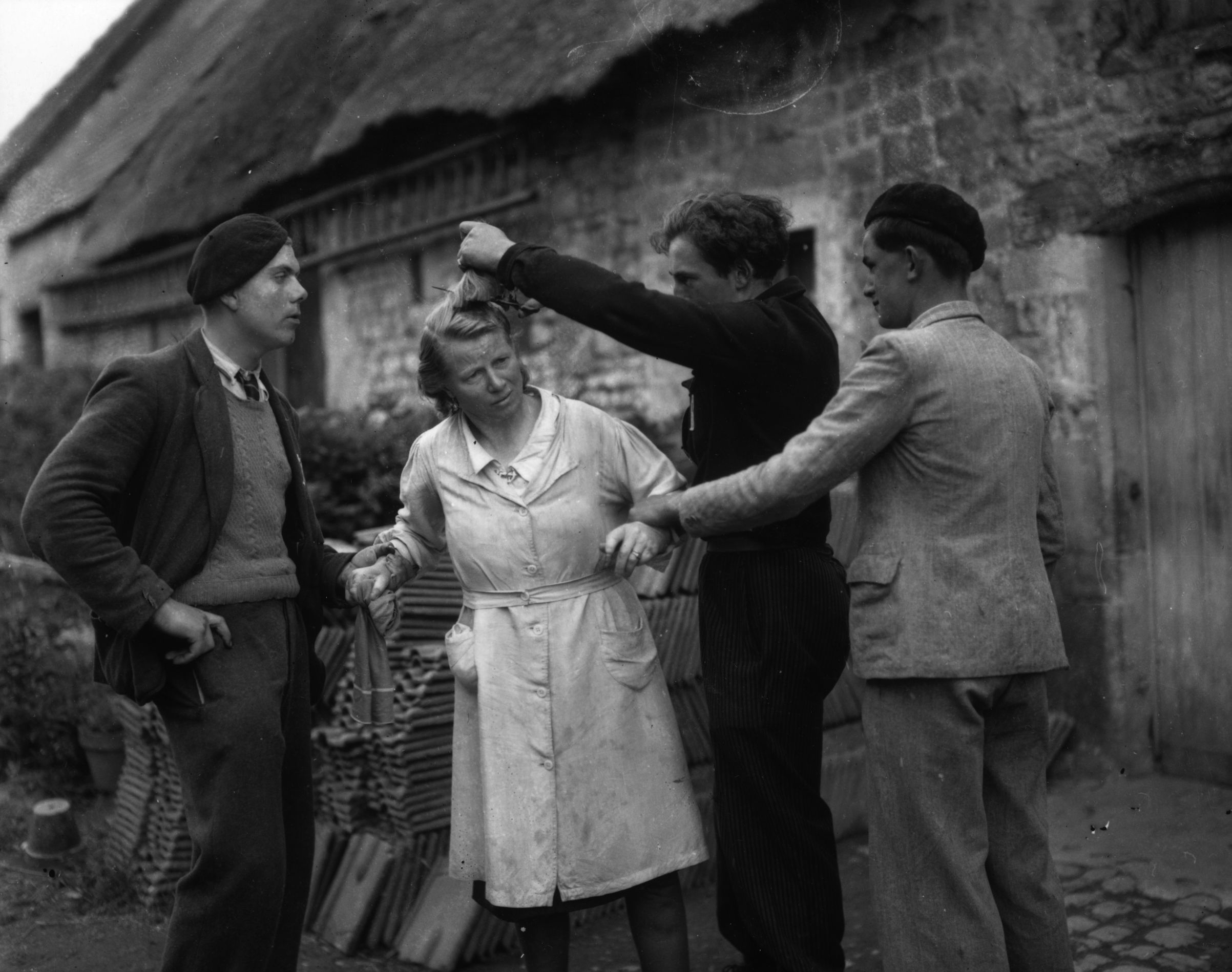circa 1945: Two French men restrain a woman while another crops her hair after she has been accused of collaborating with the Germans during the occupation.