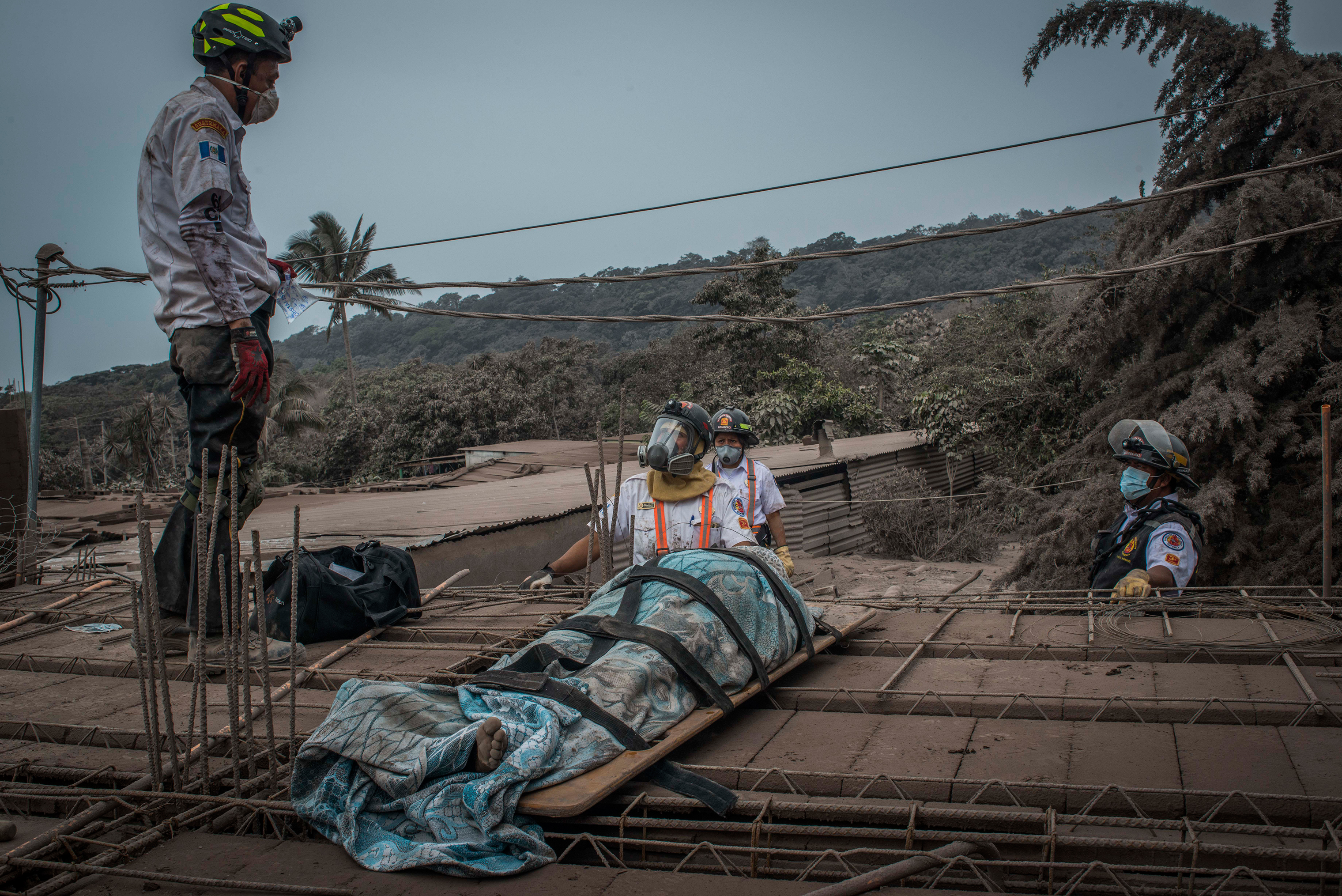 Rescuers recover a body among the ruins of the village of San Miguel Los Lotes, near the Guatemalan city of Escuintla, on June 4.