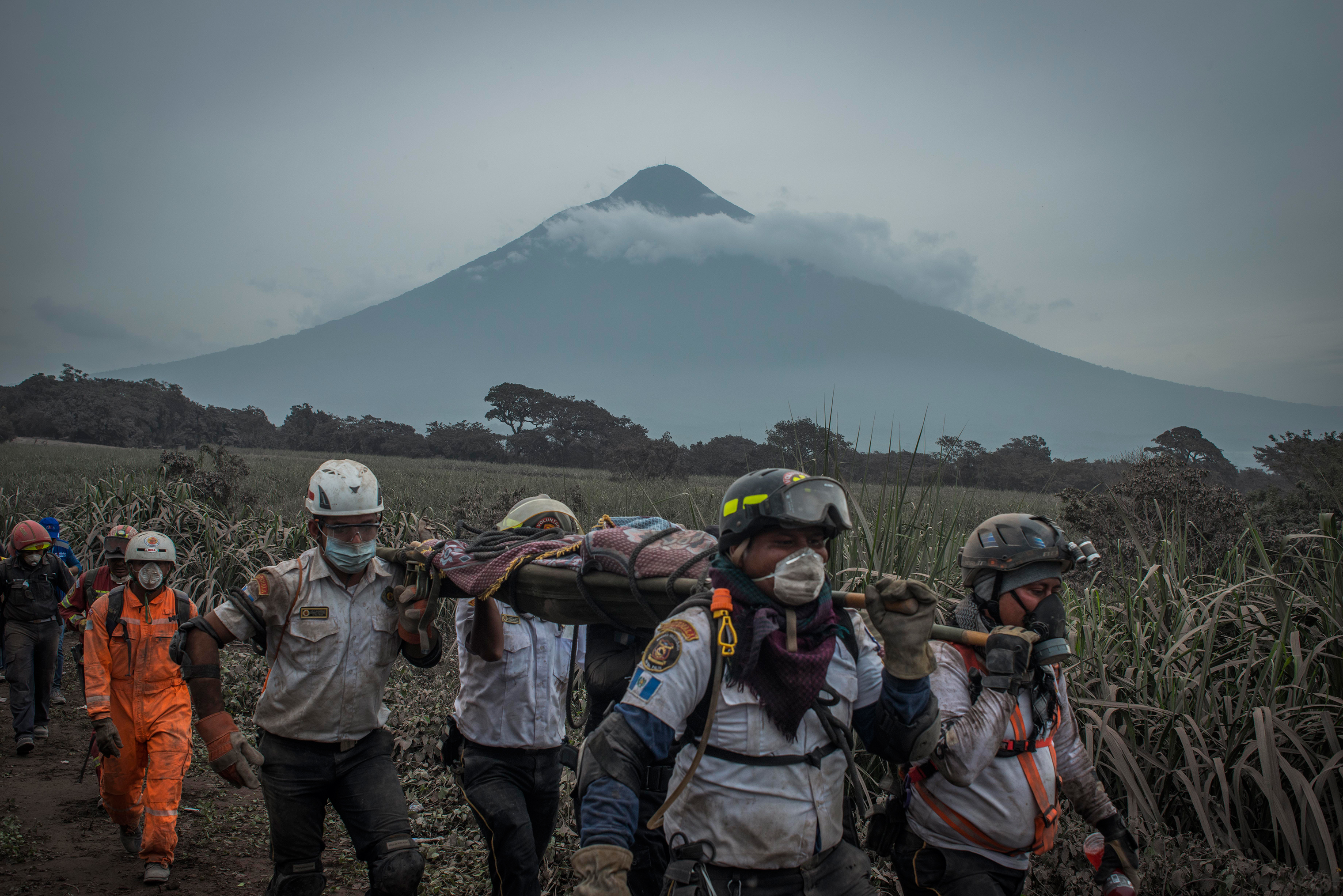 Rescuers carry a body in San Miguel Los Lotes on June 4. In the background is the Volcán de Agua, which has no history of eruptions.