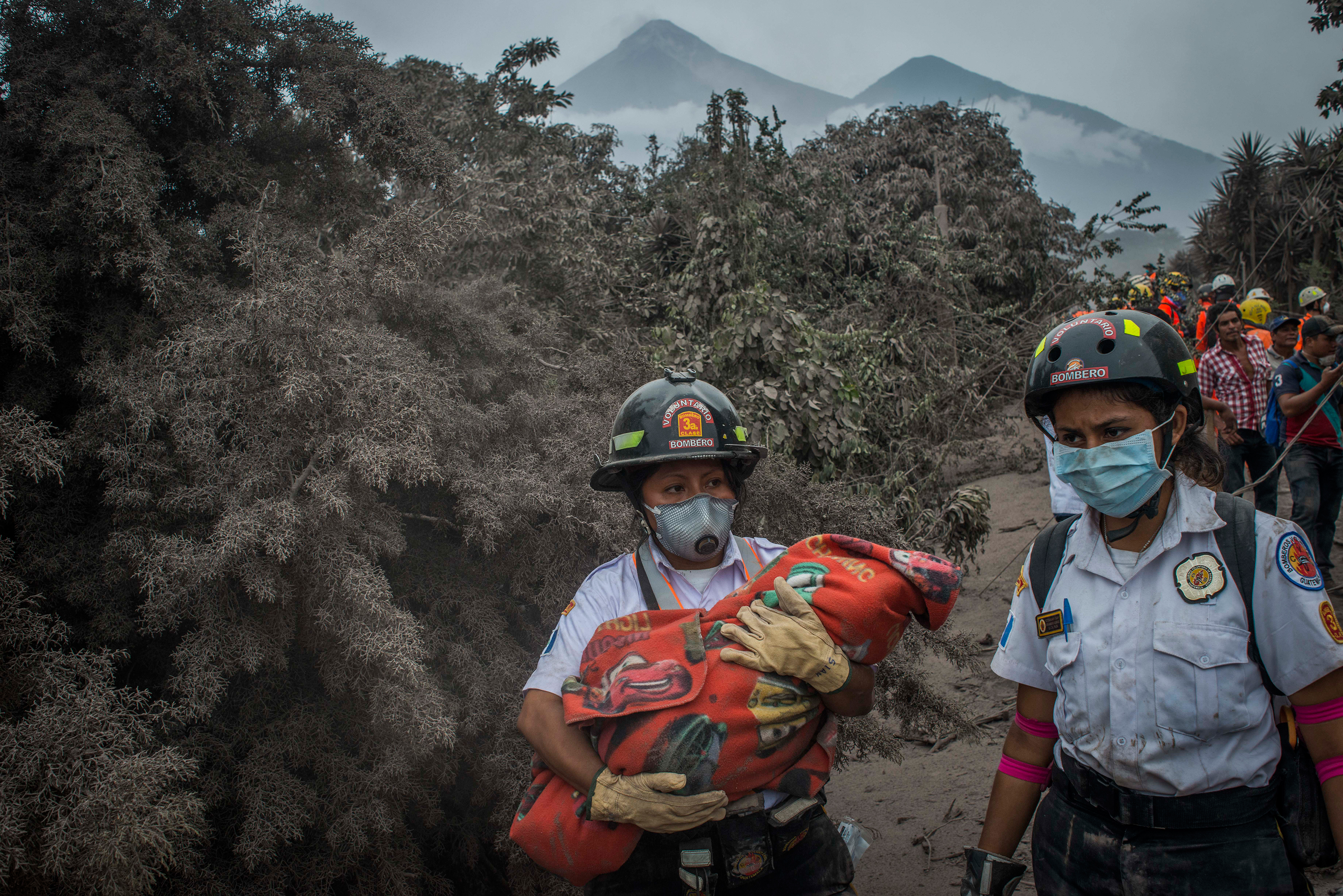 An emergency worker carries the body of a child found in the ruins of San Miguel Los Lotes on June 4.