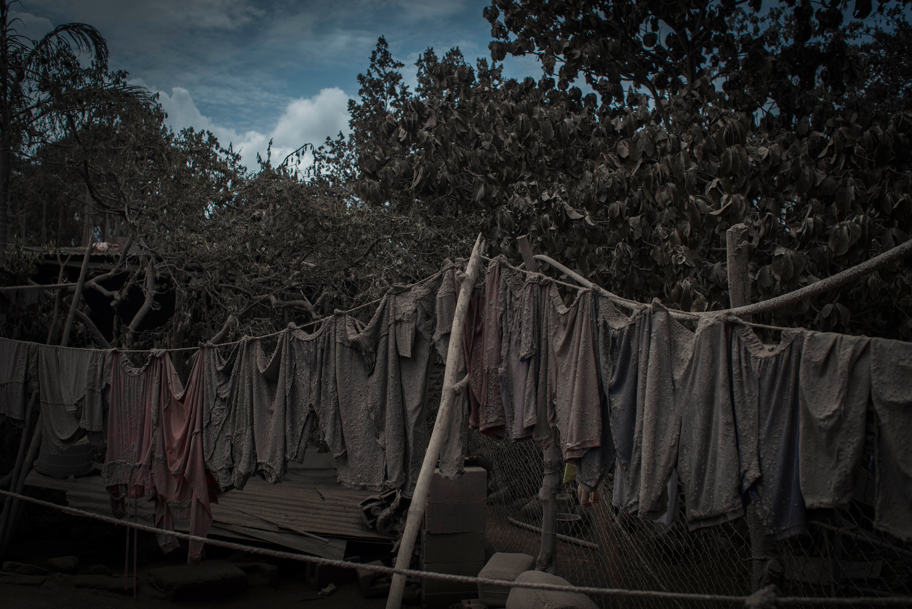 An ash-covered clothesline hangs outside a home in San Miguel Los Lotes on June 5.