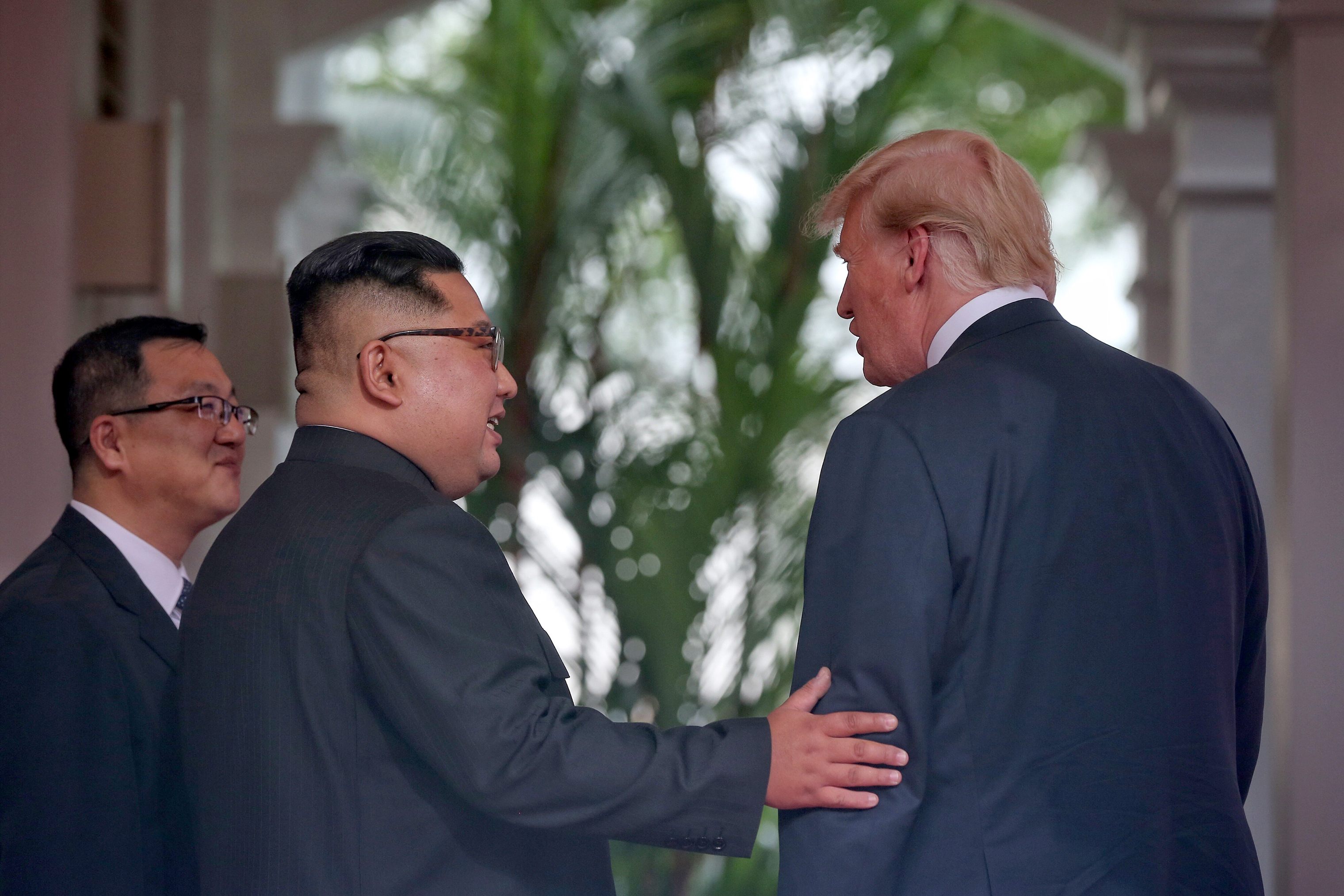 North Korean leader Kim Jong Un touches the arm of PresidentTrump shortly after meeting at their summit in Singapore on June 12, 2018.