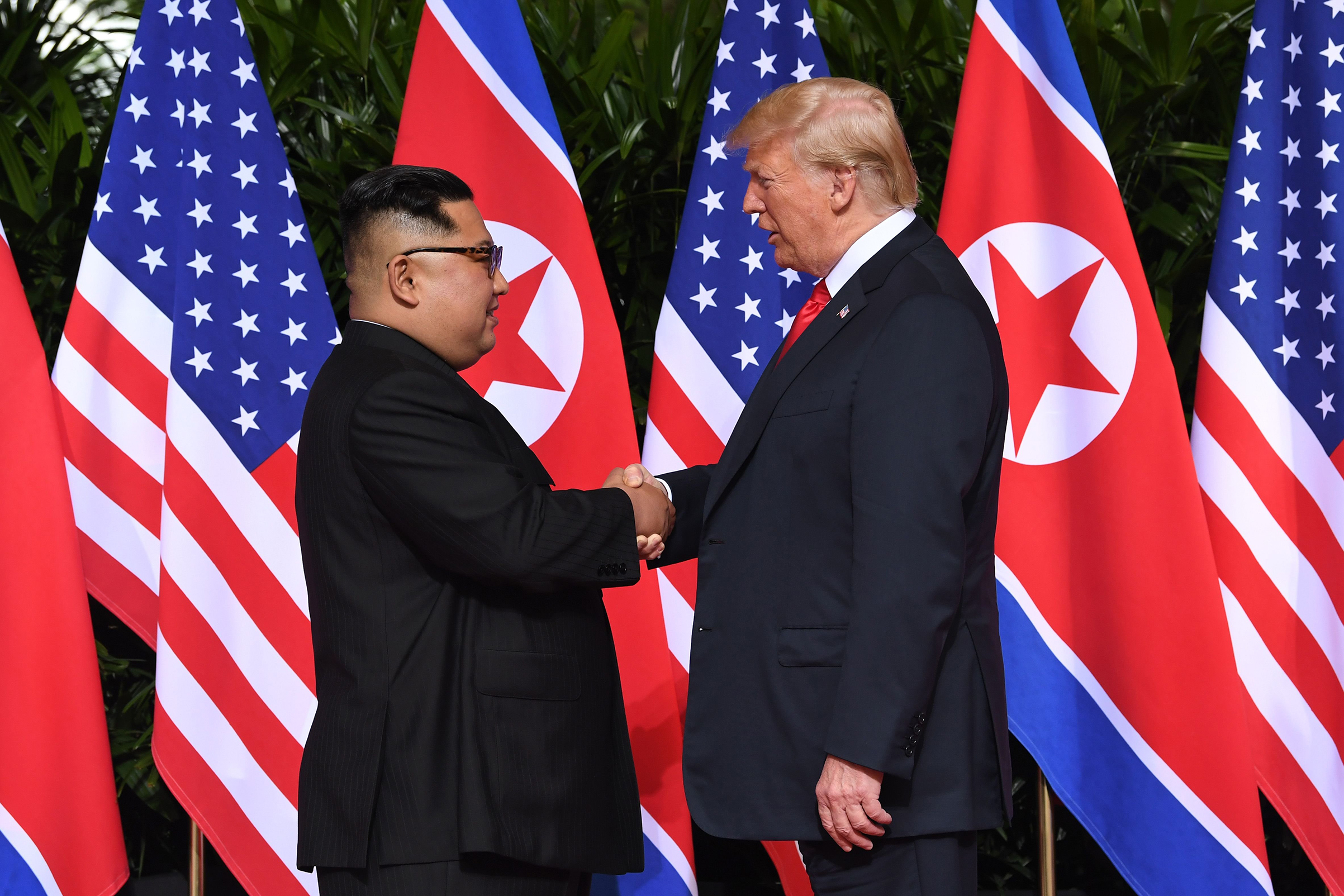 North Korean leader Kim Jong Un and President Trump shake hands at the start of their historic summit at the Capella Hotel on Sentosa island in Singapore on June 12, 2018.