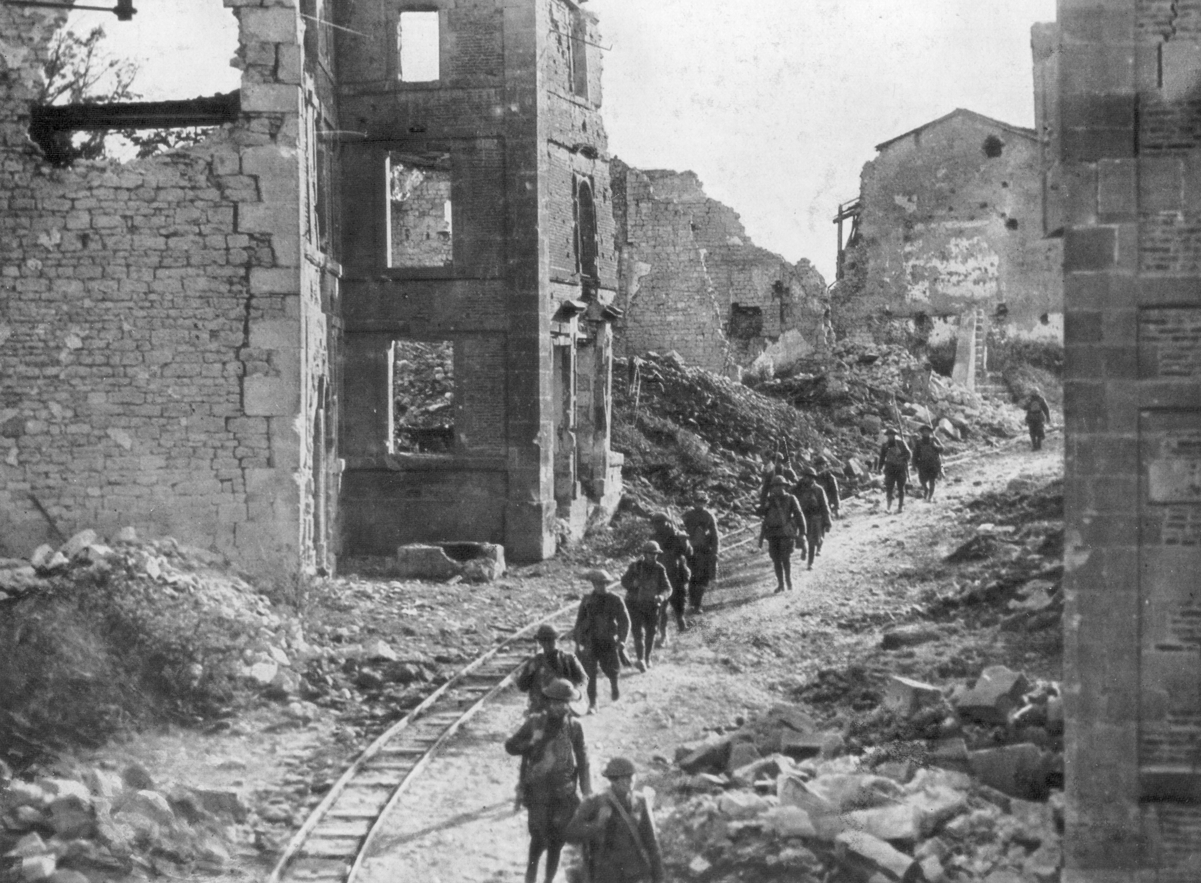 American soldiers passing through the ruins of Varennes, Meuse-Argonne Offensive, France, 1918.
