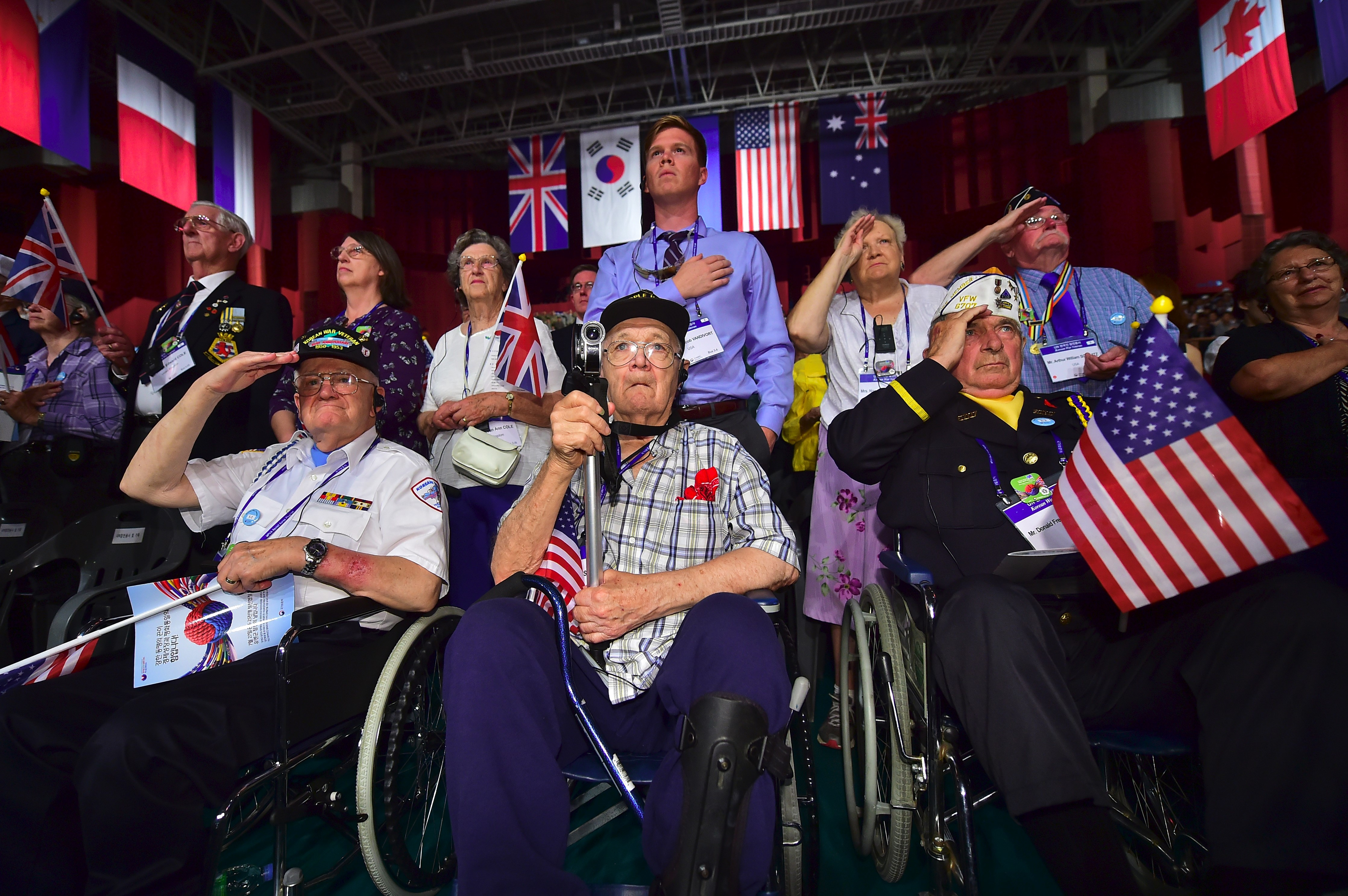 Invited US veterans, who fought in the Korean War under the United Nations flag, and their family members salute during a ceremony to commemorate the 63rd anniversary of the Korean War Armistice Agreement in Seoul on July 27, 2016.