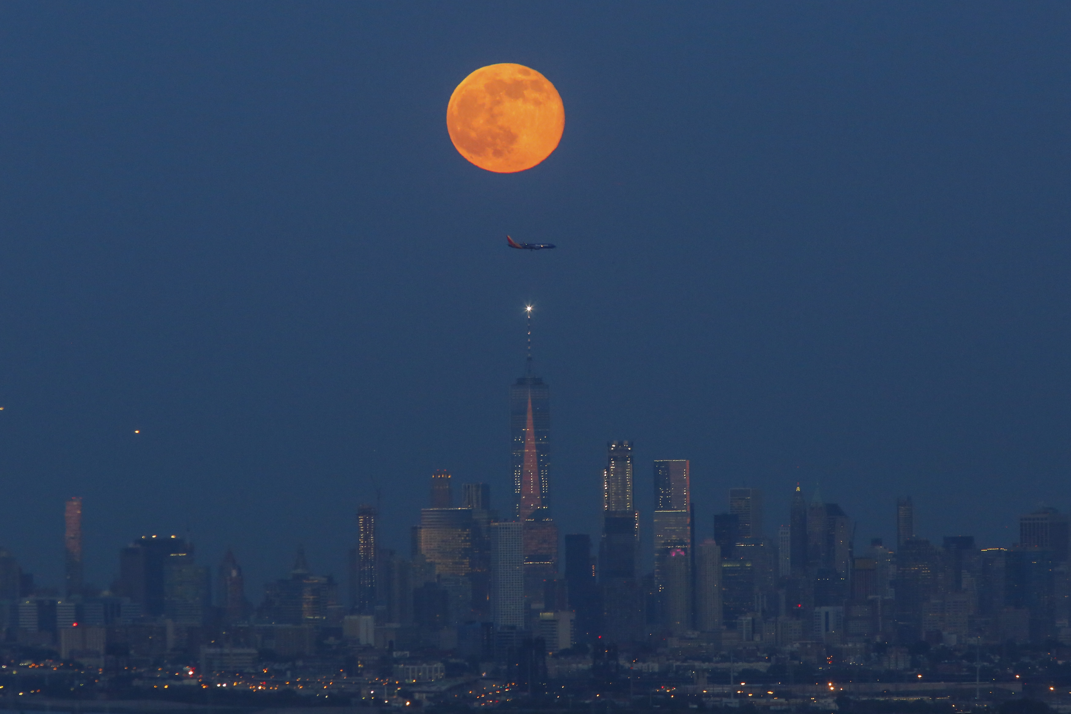 The Strawberry Moon rises over lower Manhattan and One World Trade Center on June 06, 2017 in Montclair, New Jersey. (Photo by Kena Betancur/VIEWpress/Corbis via Getty Images)