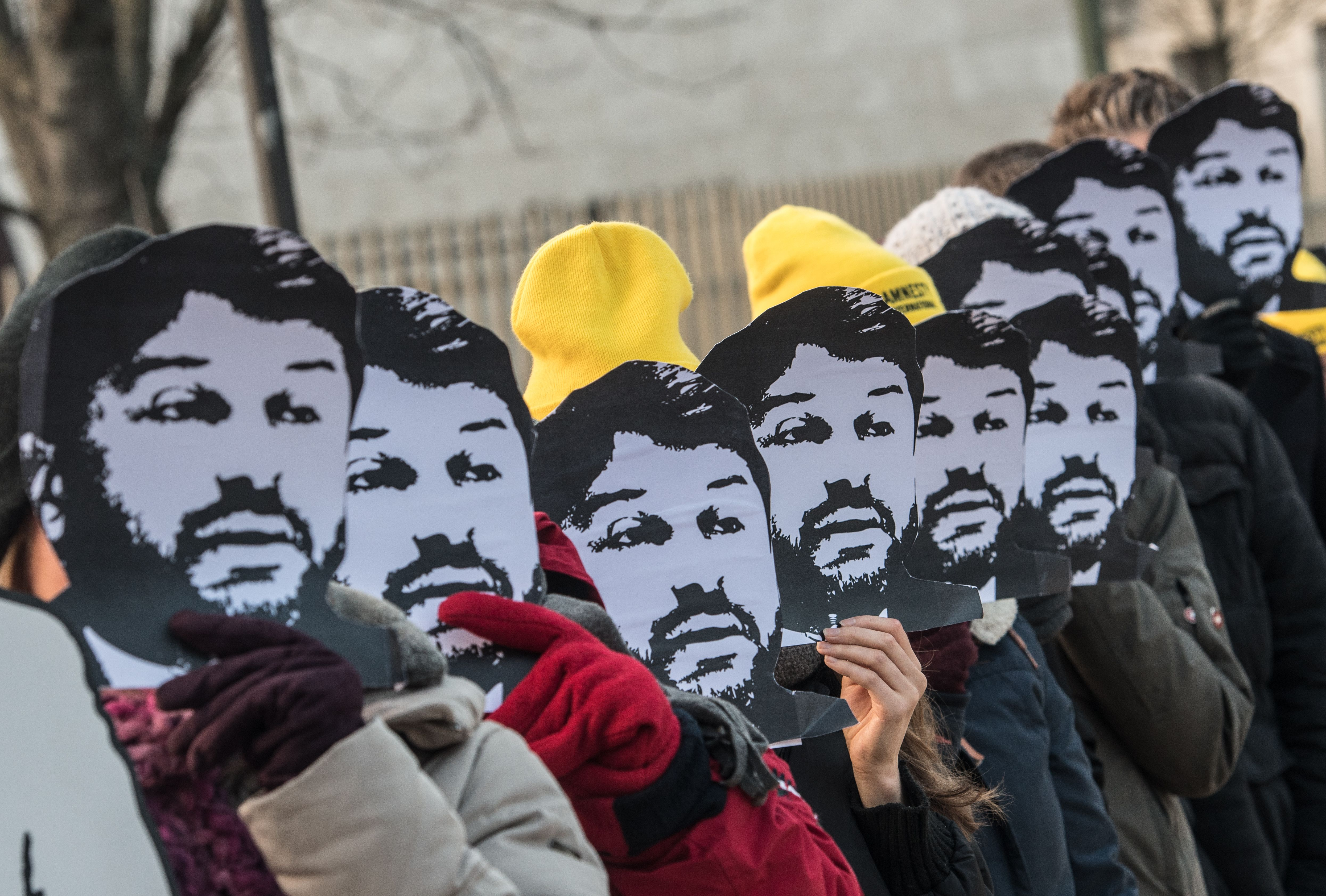 Activists of the human rights organization Amnesty International hold masks of Turkish civil rights activist Taner Kilic in front of their faces as they demonstrate on February 7, 2018 in front of the Turkish embassy in Berlin.
