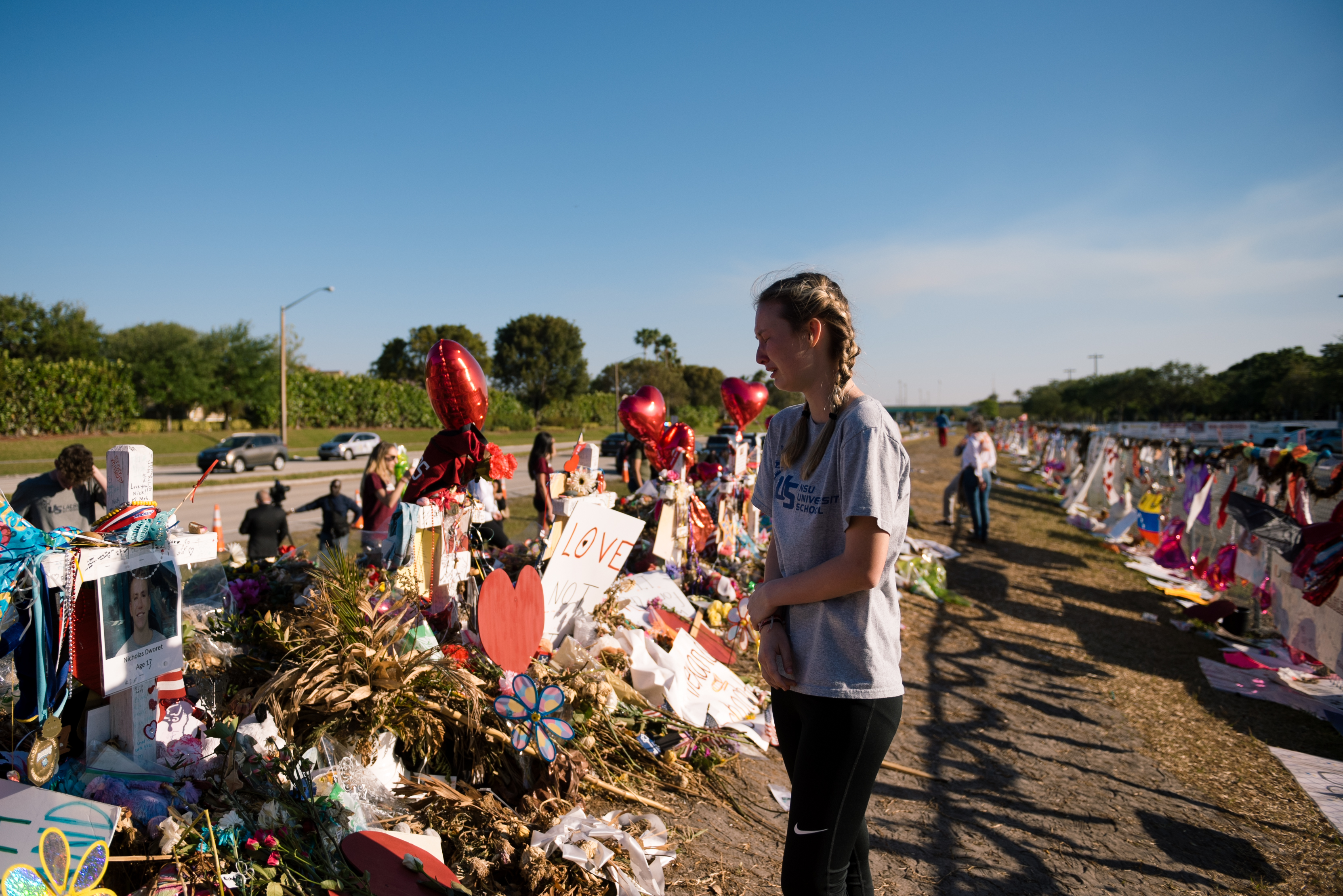A student visits the memorial site of the 17 lives lost at Marjory Stoneman Douglas.