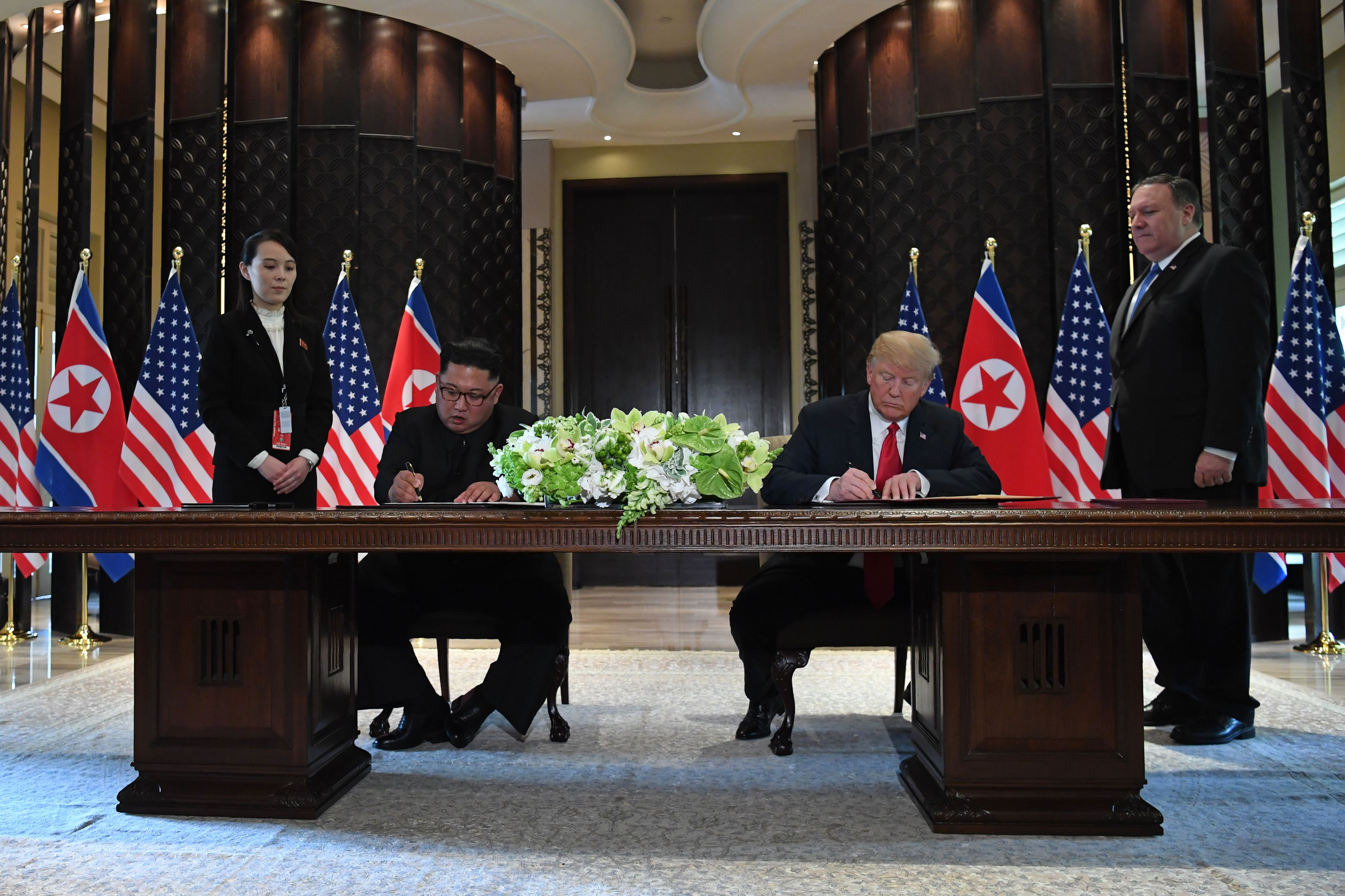 President Donald Trump and North Korea's leader Kim Jong Un sign documents as U.S. Secretary of State Mike Pompeo and the North Korean leader's sister Kim Yo Jong look on at a signing ceremony at the Capella Hotel on Sentosa island in Singapore on June 12, 2018.