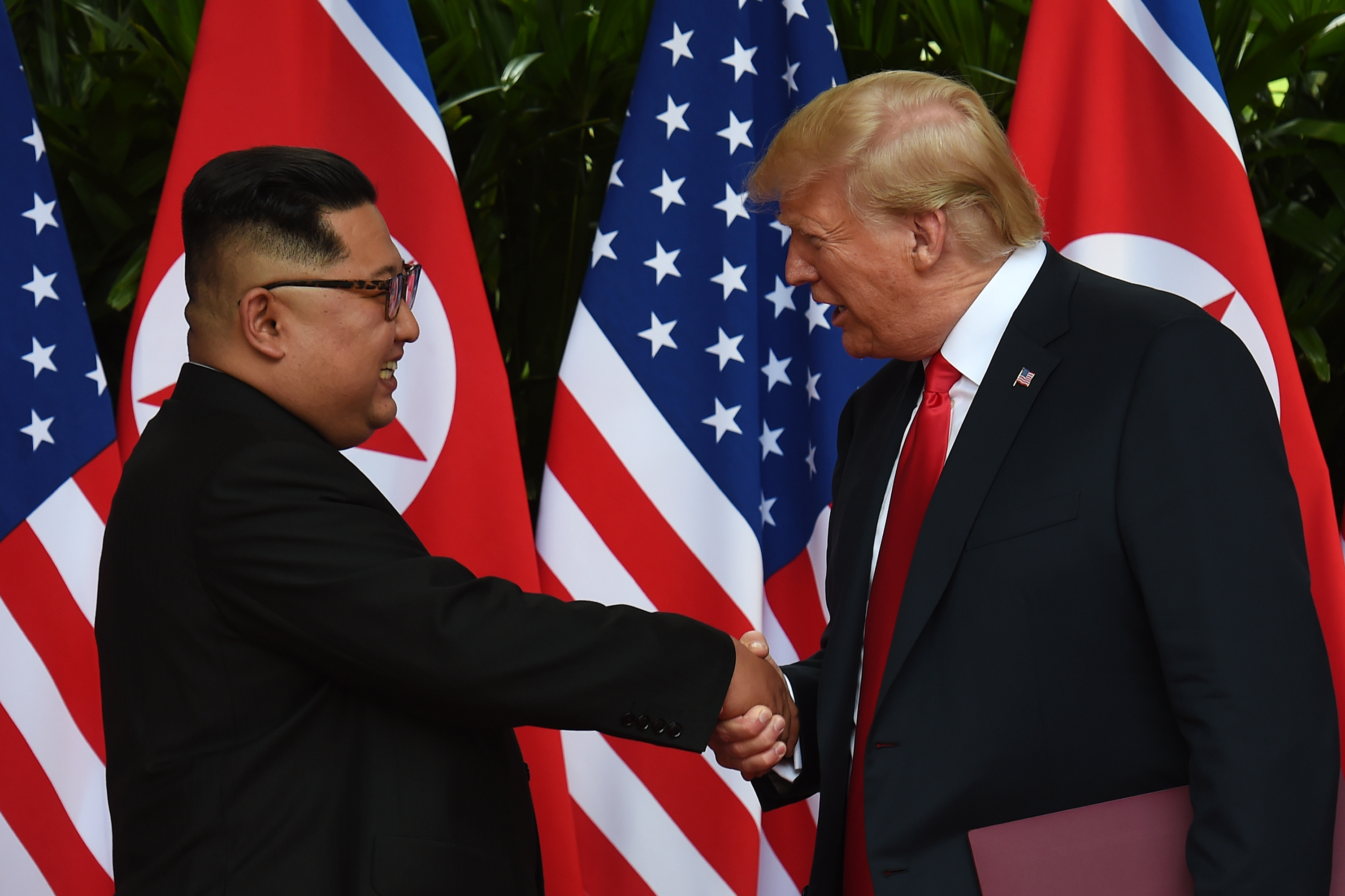 North Korea's leader Kim Jong Un (L) shakes hands with U.S. President Donald Trump after taking part in a signing ceremony at the end of their historic U.S.-North Korea summit, at the Capella Hotel on Sentosa island in Singapore on June 12, 2018.