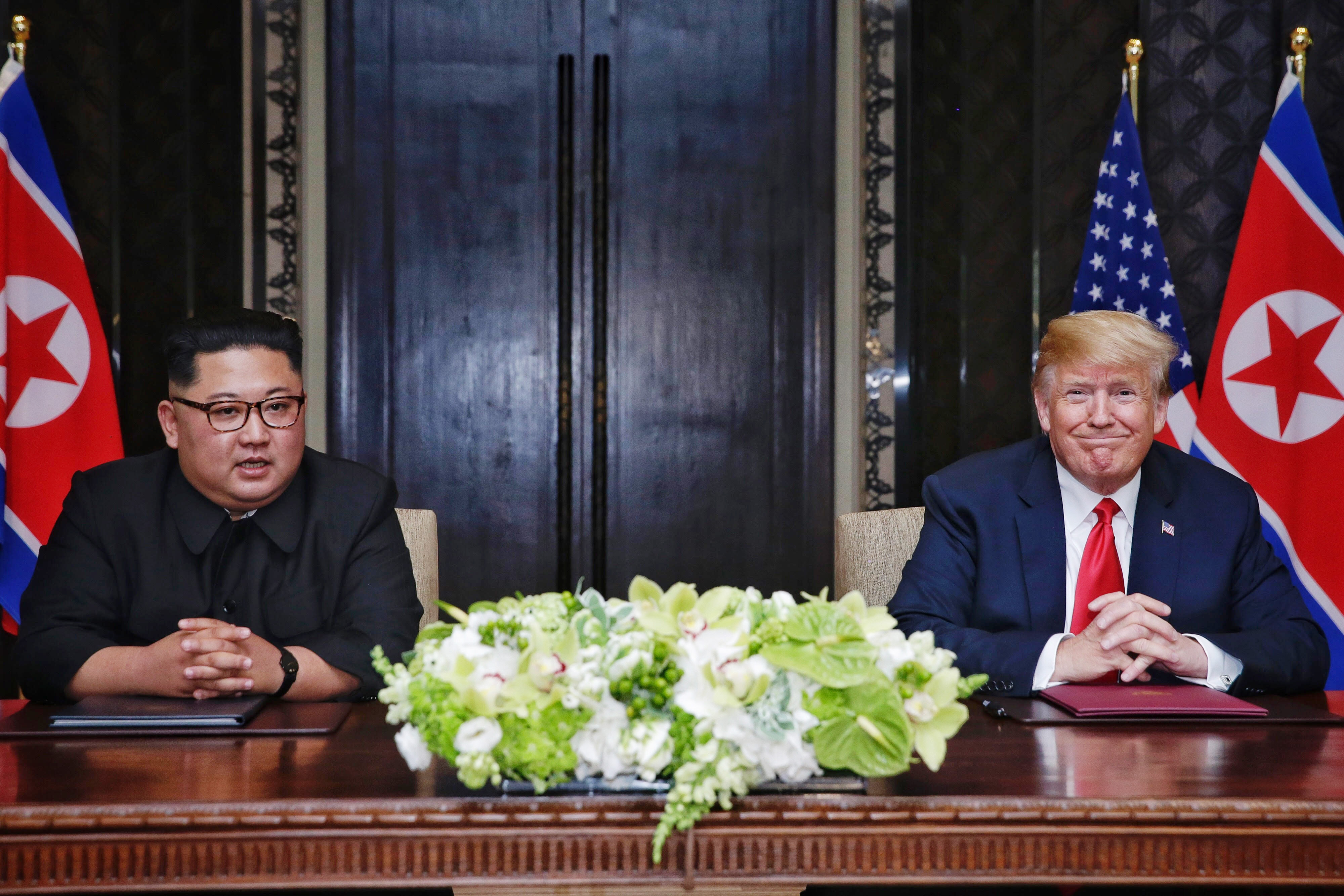 North Korean leader Kim Jong-un (L) with U.S. President Donald Trump (R) during their historic U.S.-DPRK summit at the Capella Hotel on Sentosa island on June 12, 2018 in Singapore