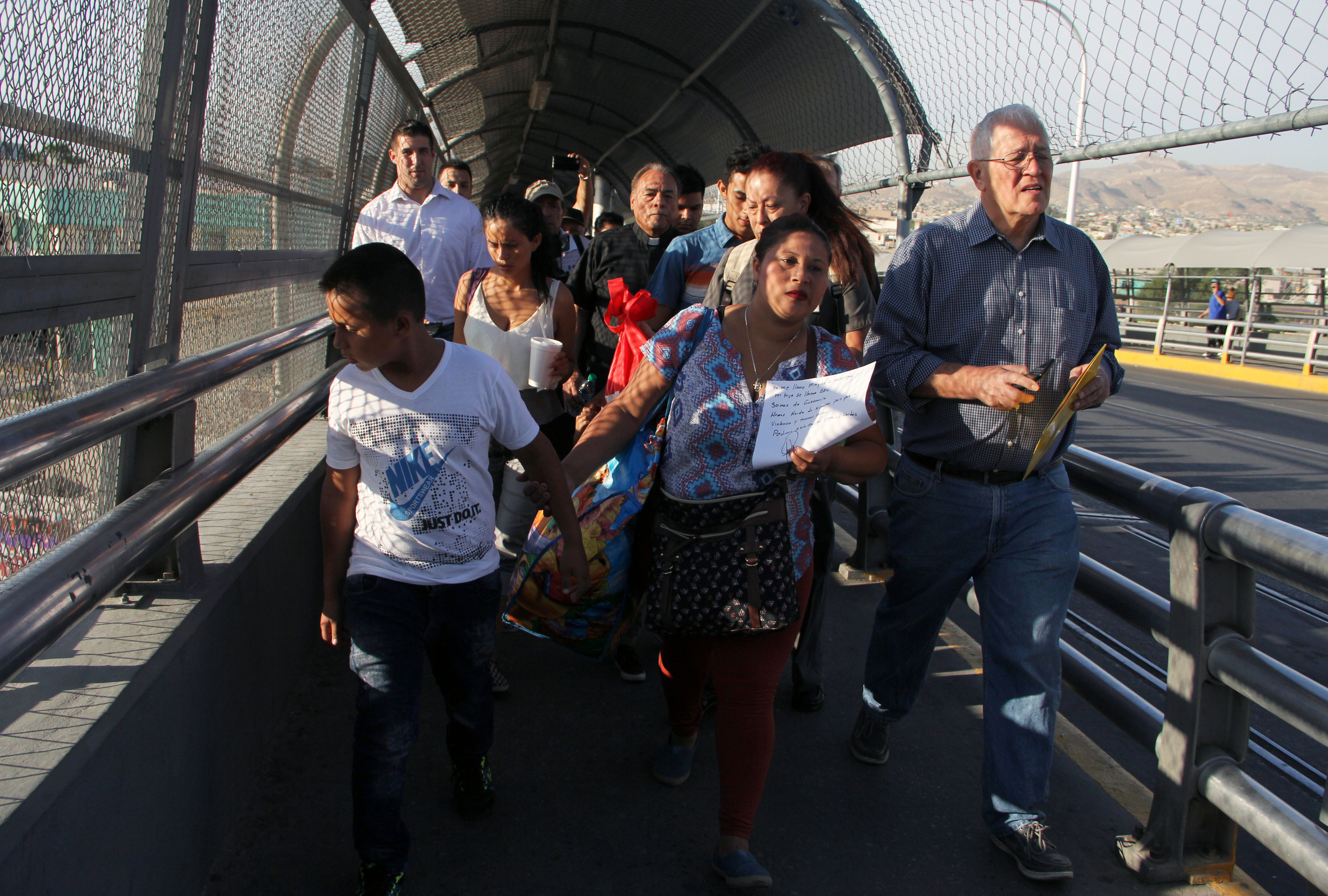U.S. activist Ricardo Garcia (R) from Casa Asuncion shelter, accompanies six Honduran and Guatemalan migrants to ask for political asylum in U.S., at the Paso del Norte International Bridge, in Ciudad Juarez Chihuahua, Mexico on the border with El Paso, Texas, US, on June 15, 2018.