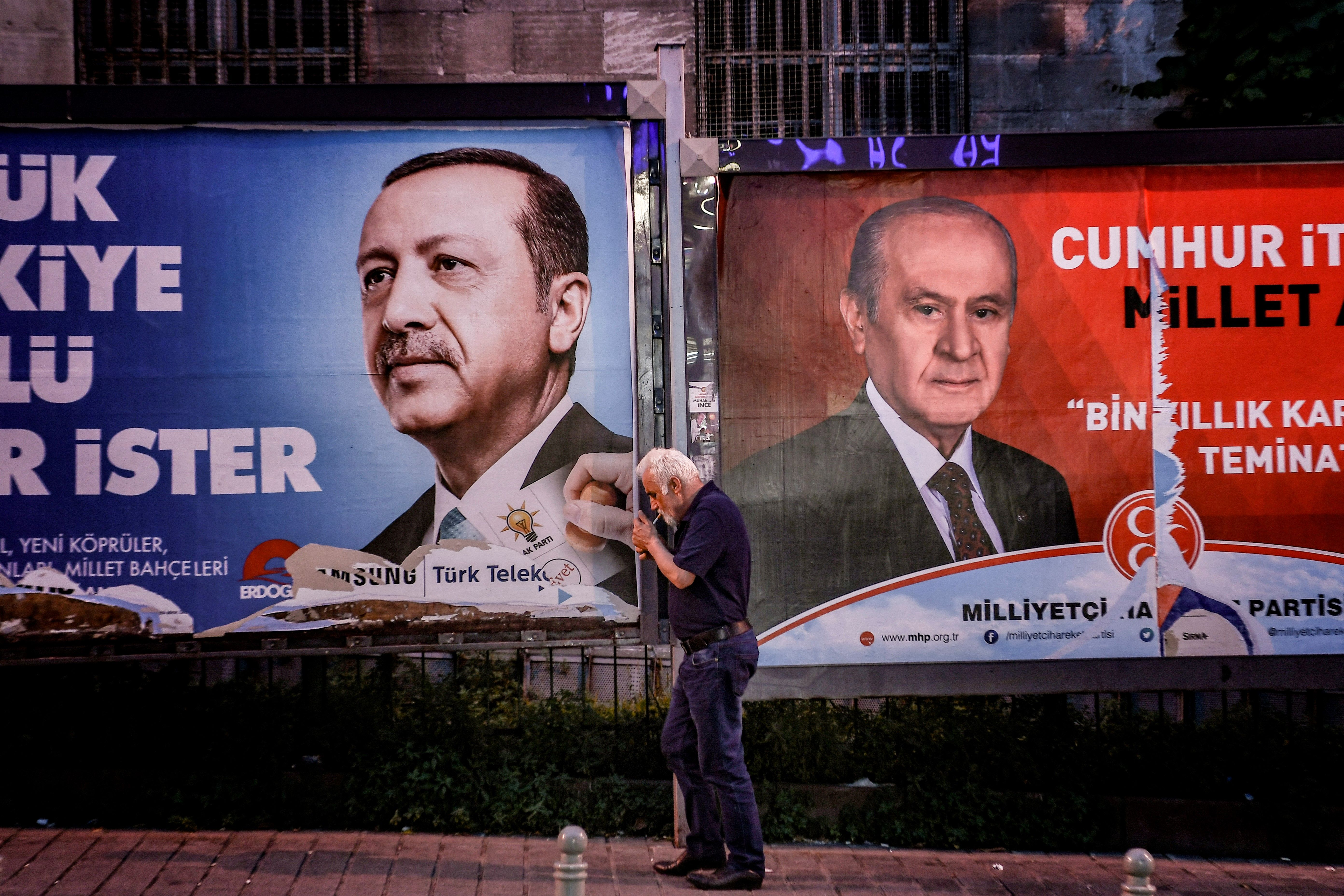 A pedestrian lights a cigarette as he walks past in banners with portraits of Turrkish President Recep Tayyip Erdogan (L) and the leader of Nationalist Movement Party (MHP) Devlet Bahceli in Istanbul on June 19, 2018.