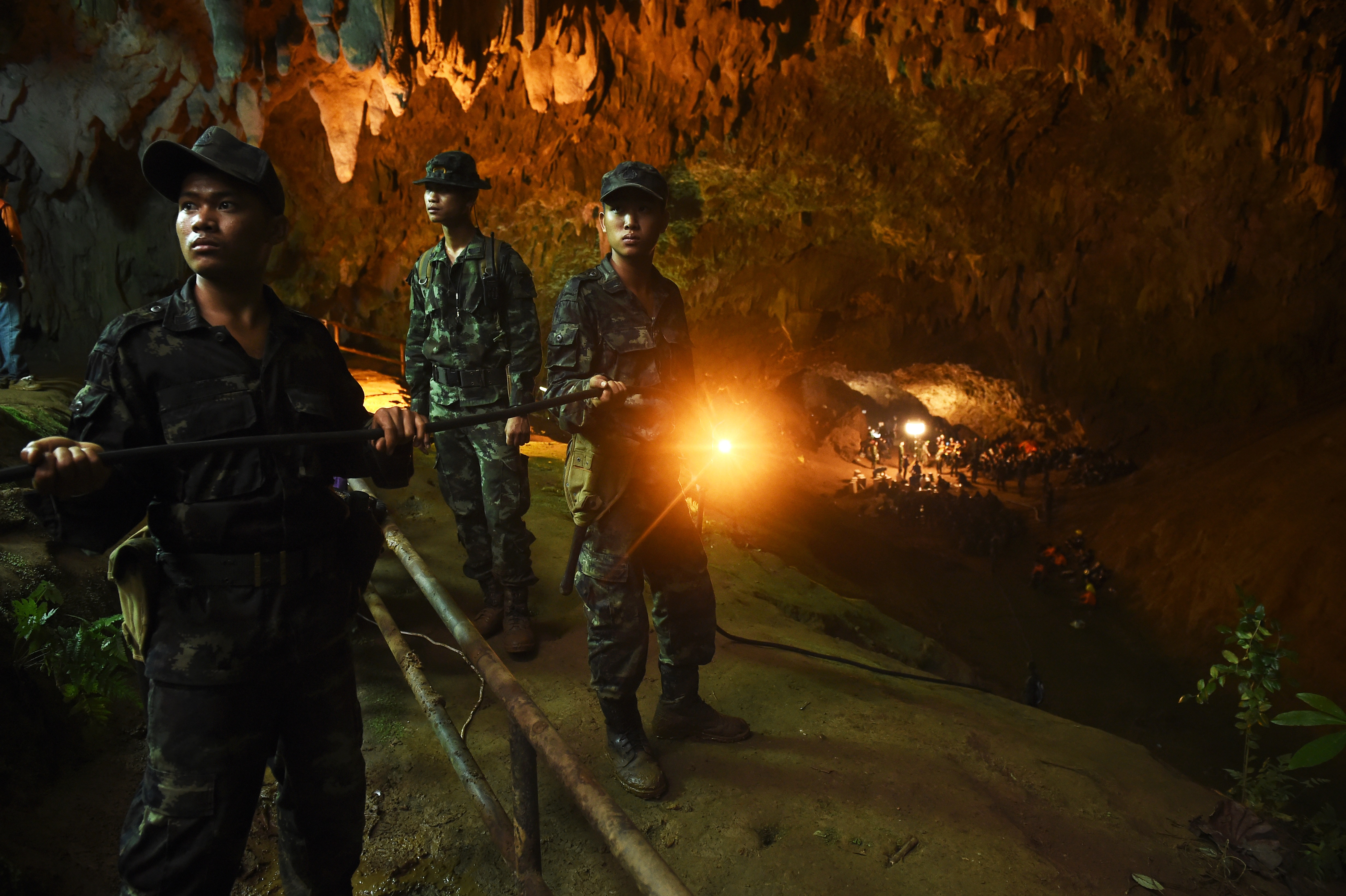 Thai soldiers relay electric cable deep into the Tham Luang cave at the Khun Nam Nang Non Forest Park in Chiang Rai on June 26, 2018.