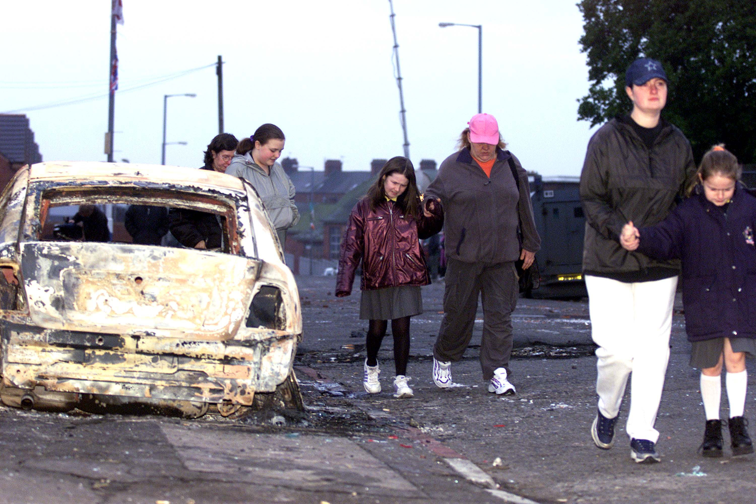 Local residents of the Glenbryn area in North Belfast walk past burnt-out remains of an armored police car following overnight rioting between Nationalists and Loyalists crowds January 10, 2002 in Belfast, Northern Ireland. Rioting erupted as Catholic parents picked up their children from the Holy Cross girls'' primary school.