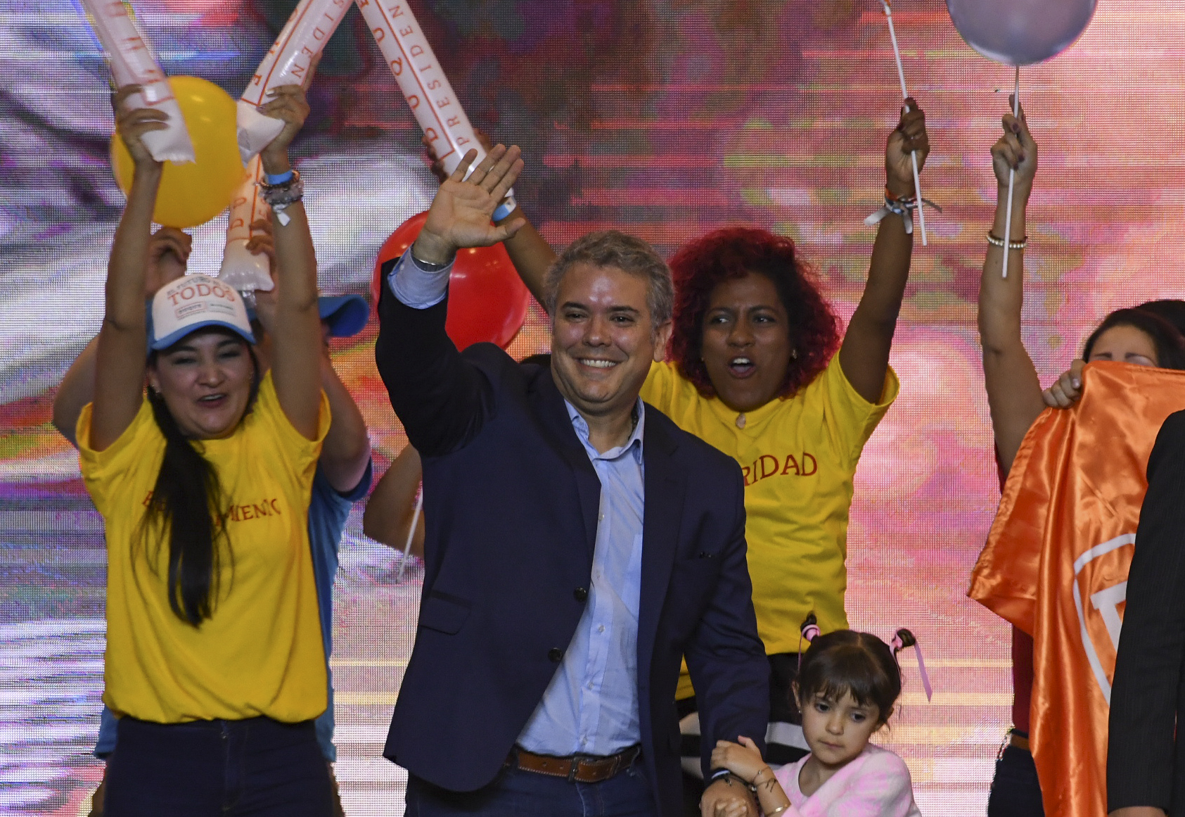 Colombian presidential candidate Ivan Duque, for the Democratic Centre party, holds his daughter's hand, as he waves to supporters in Bogota, after winning the first round of the Colombian presidential election on May 27, 2018.