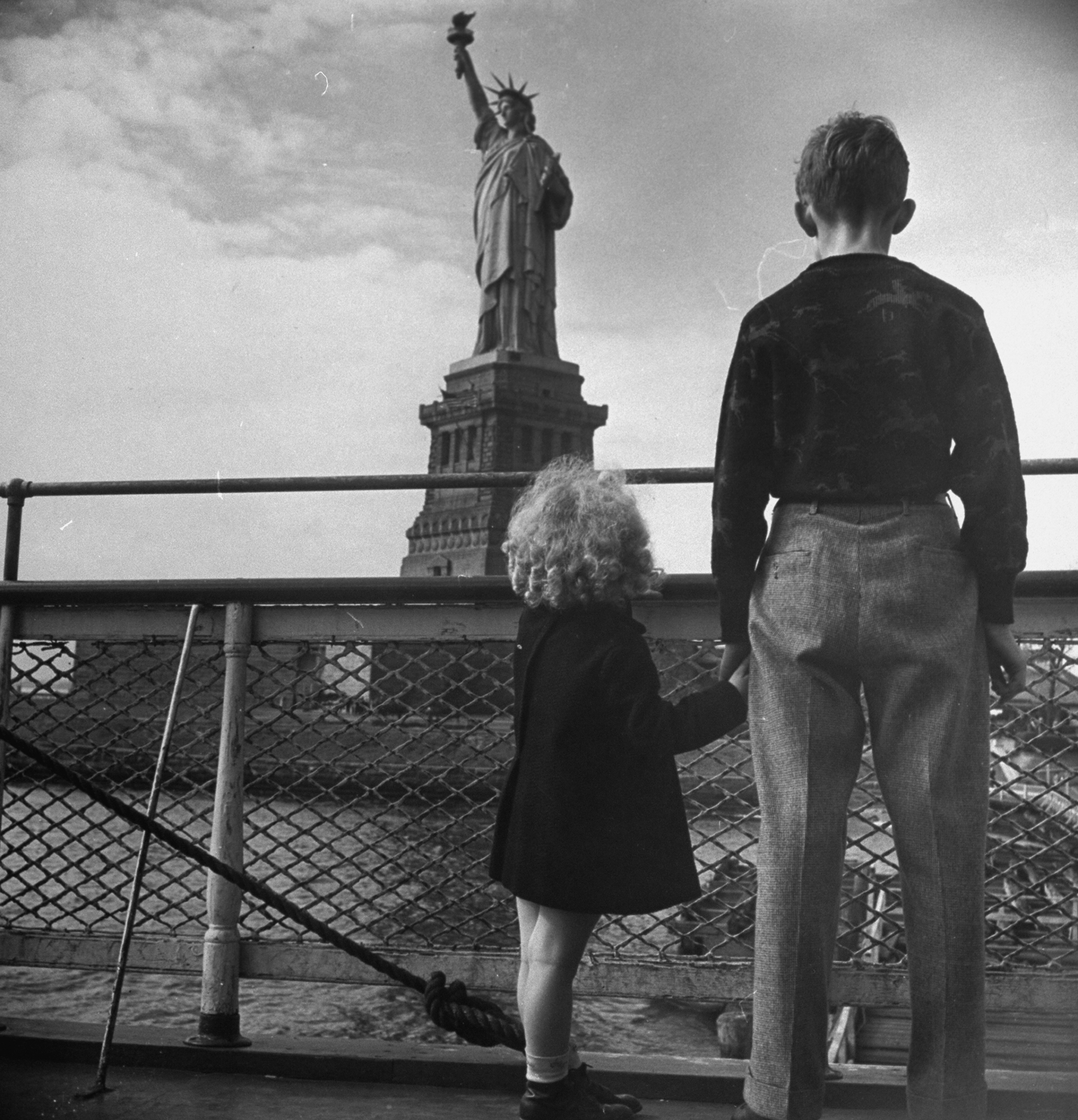 Refugee children gazing at Statue of Liberty from railing of boat, ca. 1946.