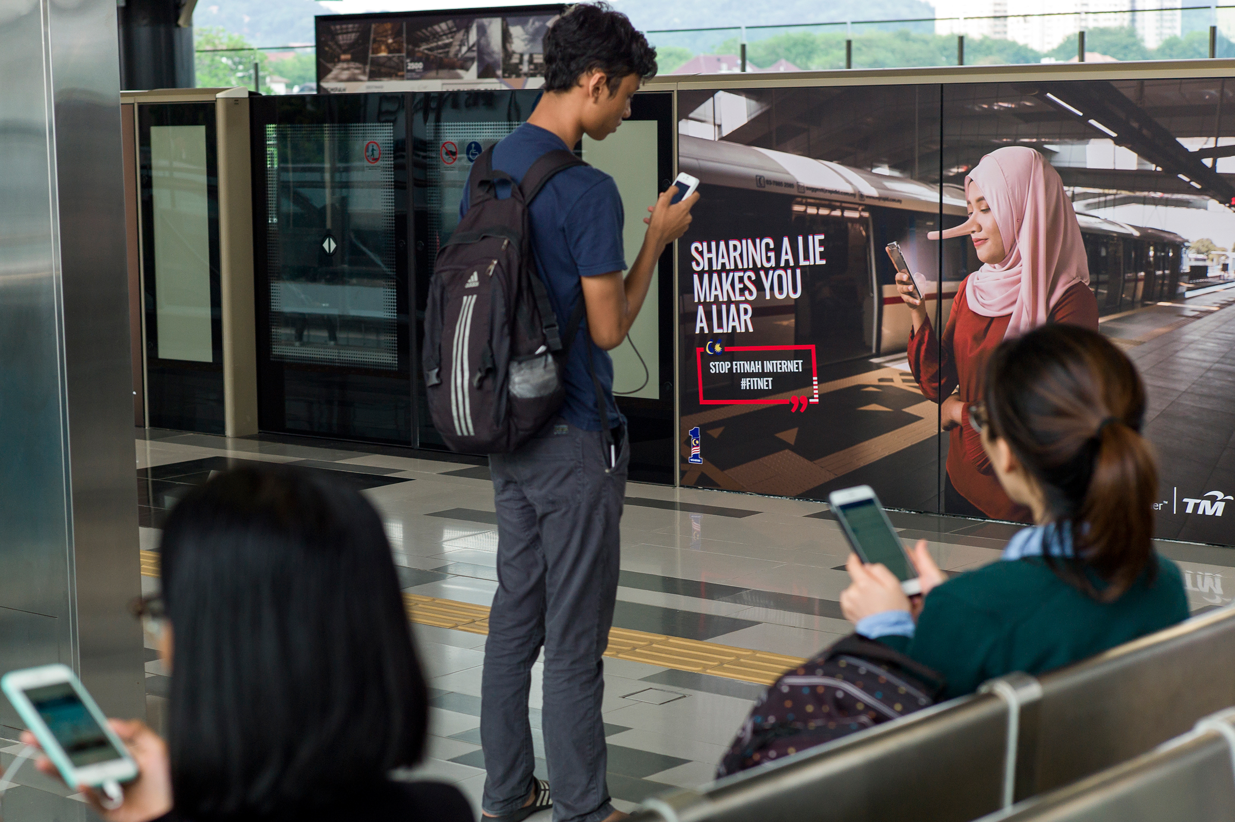 Commuters use their smartphones near an advertisement that reads  SHARING A LIE MAKES YOU A LIAR  at a train station in Kuala Lumpur on March 26, 2018.