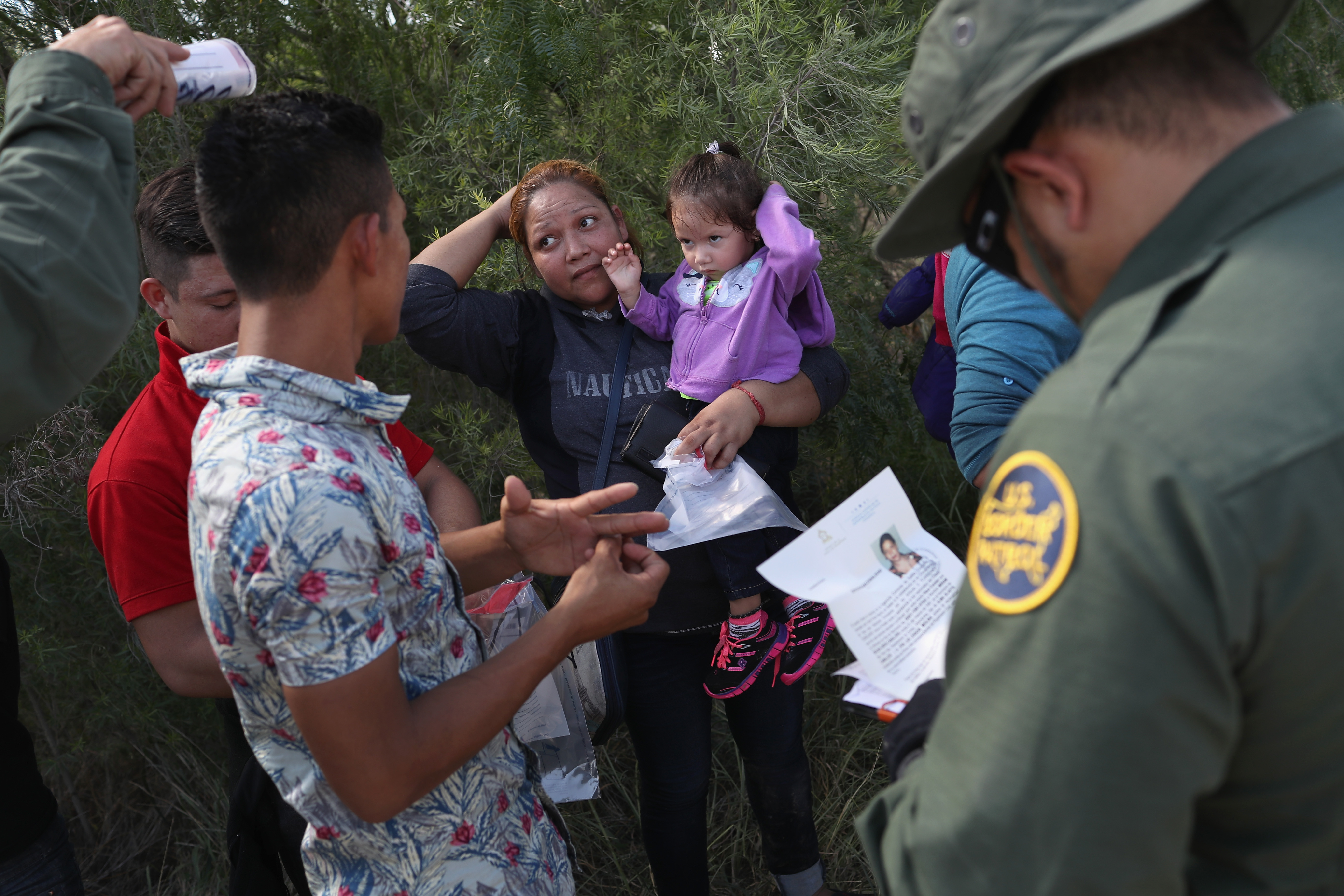 U.S. Border Patrol agents ask a group of Central American asylum seekers to remove hair bands and wedding rings before taking them into custody on June 12, 2018 near McAllen, Texas. The immigrant families were then sent to a U.S. Customs and Border Protection (CBP) processing center for possible separation. U.S. border authorities are executing the Trump administration's  zero tolerance  policy towards undocumented immigrants. U.S. Attorney General Jeff Sessions also said that domestic and gang violence in immigrants' country of origin would no longer qualify them for political asylum status.