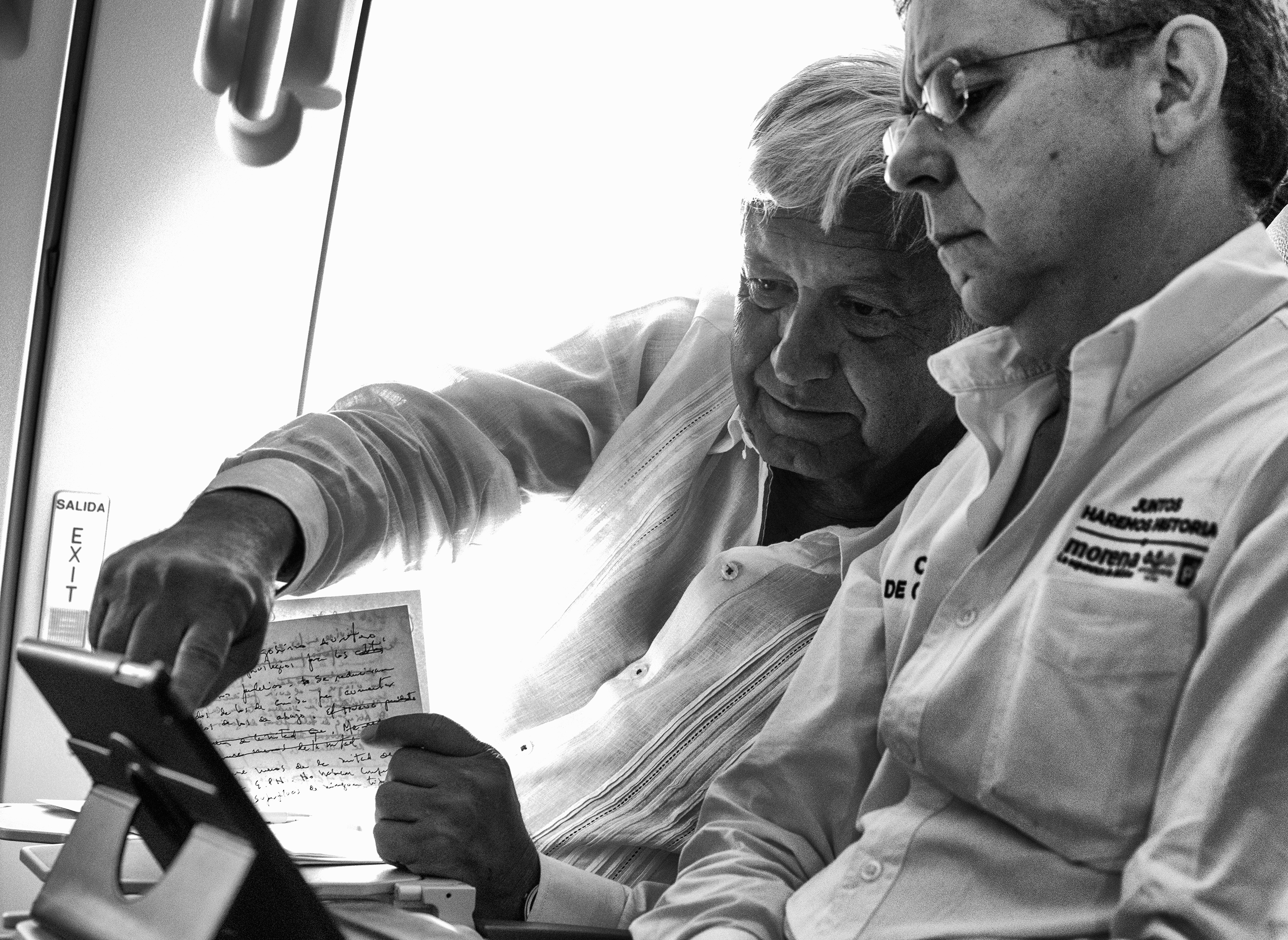 López Obrador works on a final campaign speech, alongside his Press Secretary César Yáñez, on a commercial flight to Cancún ahead of the July 1 elections.