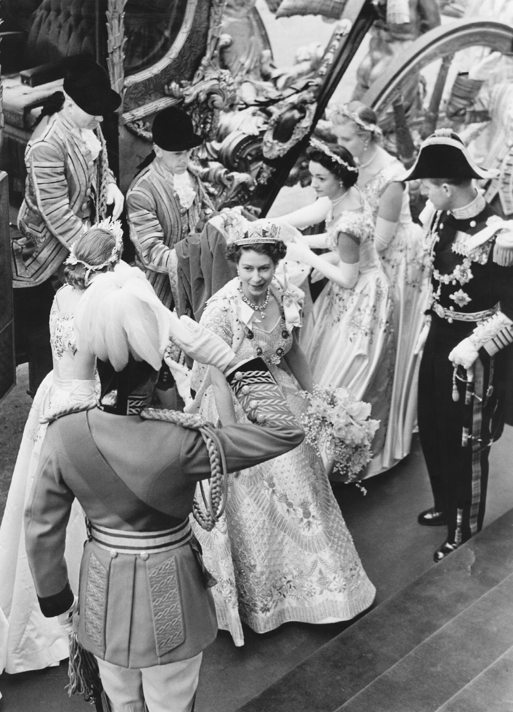 Queen Elizabeth II receives a salute from one of The Life Guards as her royal attendants help her out of her coach as she arrives to her coronation on June 2, 1953