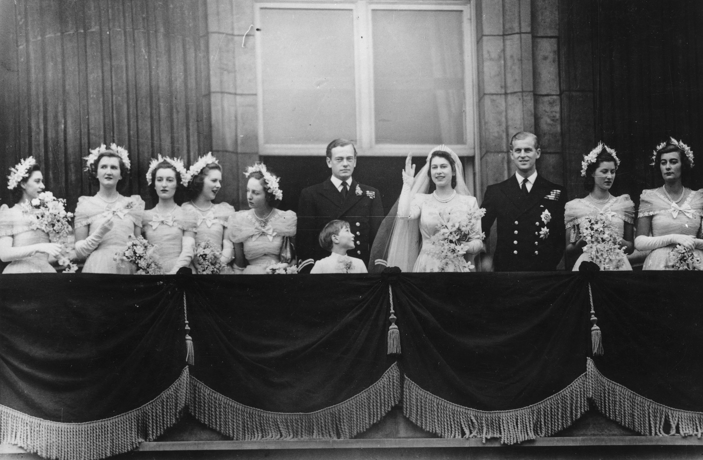 20th November 1947: The royal group on the balcony of Buckingham Palace after returning from the wedding ceremony between Princess Elizabeth and the Duke of Edinburgh at Westminster Abbey. (left to right) Princess Margaret (1930 - 2002), Margaret Elphinstone, Diana Bowes-Lyon, Lady Caroline Montague Douglas-Scott, Lady Elizabeth Lambert, the Marquis of Milford-Haven, Prince William, the bride and groom, Lady Mary Cambridge and Lady Pamela Mountbatten