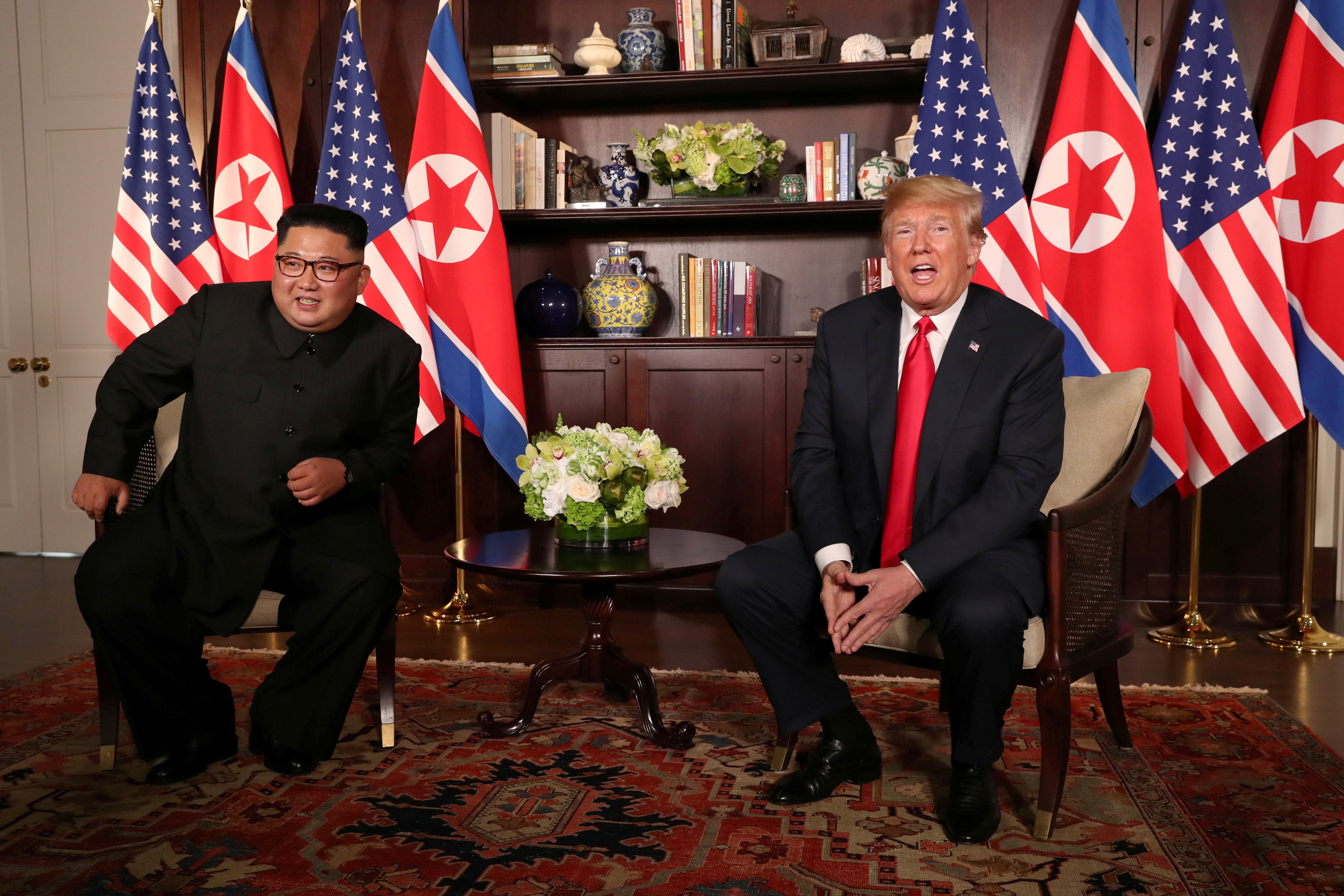 President Donald Trump sits next to North Korea's Kim Jong Un before their meeting in Singapore on June 12, 2018.