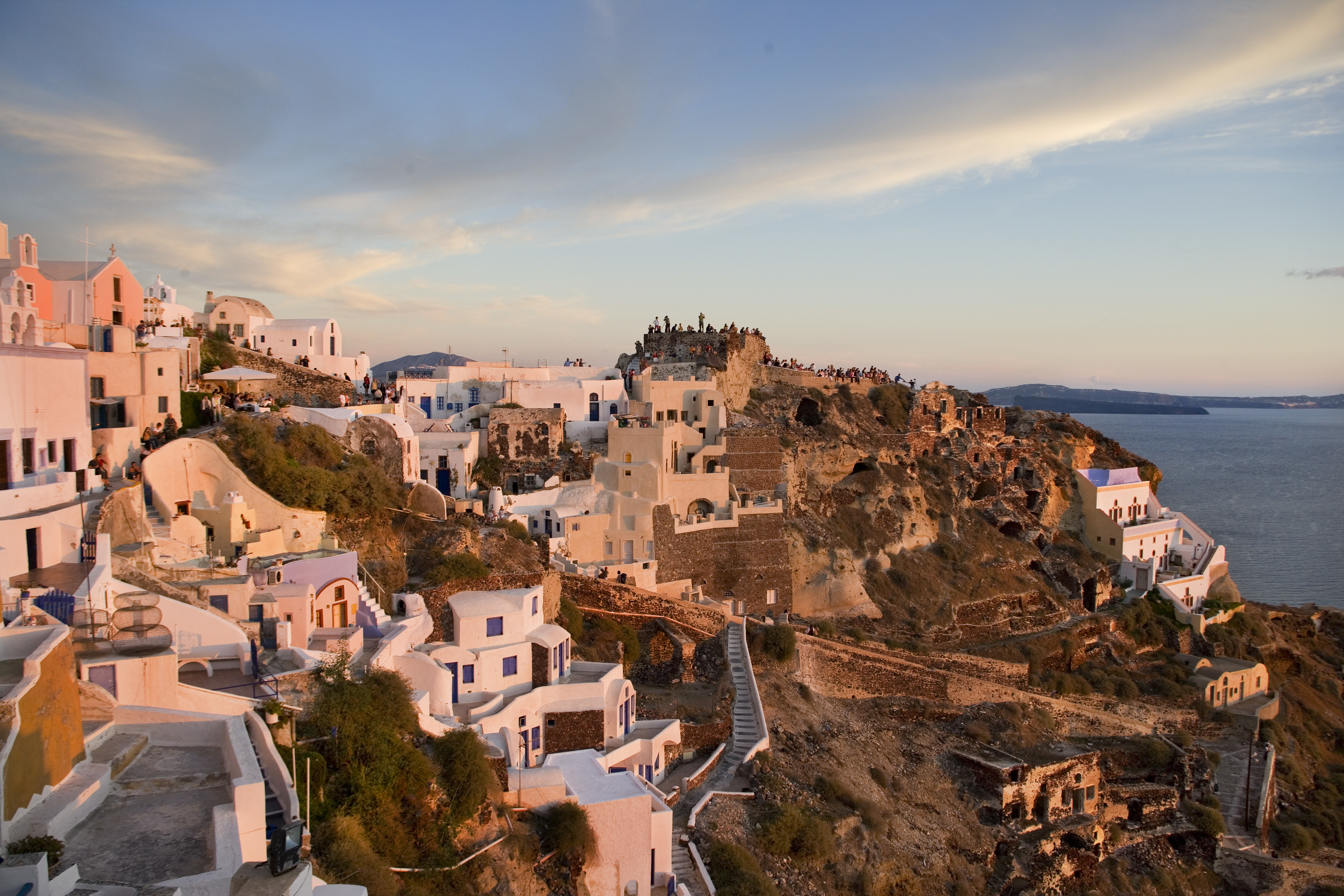 Tourists watching the sunset in Oia, the most famous of all villages of Santorini.