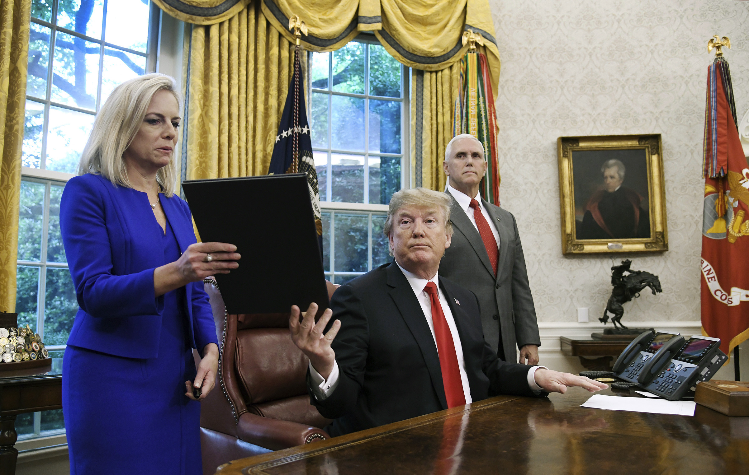 President Donald Trump gives a signed executive order to keep families together at border to Homeland Security Secretary Kirstjen Nielsen in the Oval Office of the White House, on June 20, 2018.