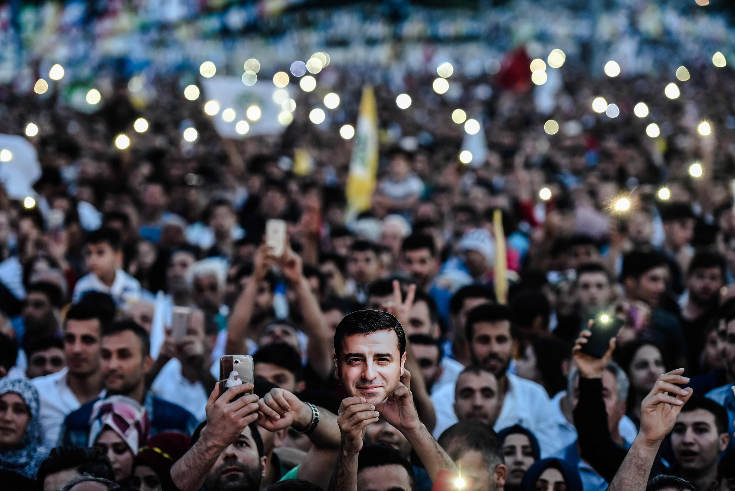 Supporters of imprisoned Selahattin Demirtas, Presidential candidate of People's Democratic Party (HDP), hold HDP flags with picture of of Demirtas during an election campaign office in Istanbul on June 17, 2018.